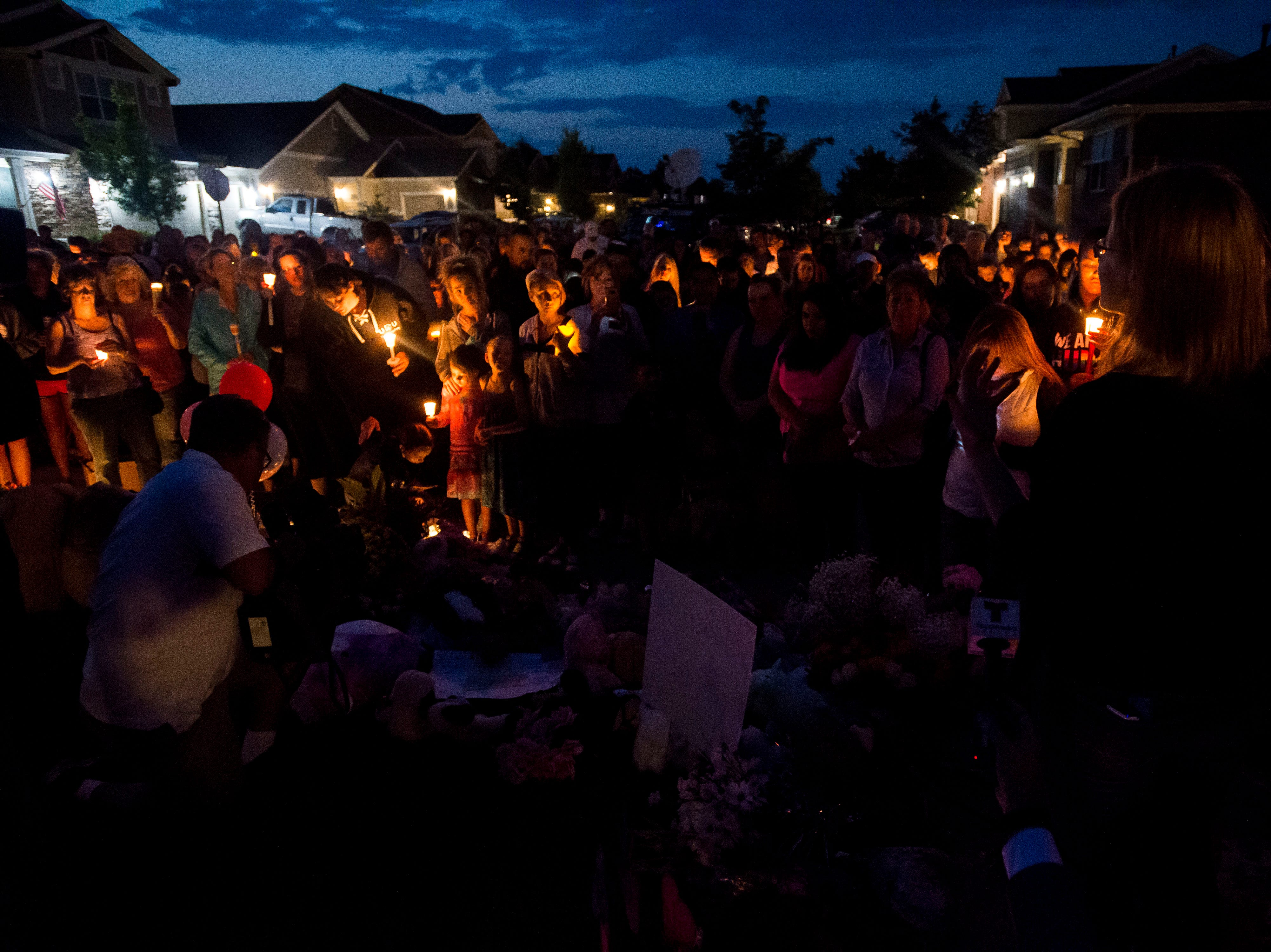 Mourners gather for a candle-lit vigil for the slain Shanann Watts and her two daughters, Bella, 4, and Celeste, 3, in front of the Watts' family home on Friday, Aug. 17, 2018, in Frederick, Colo.