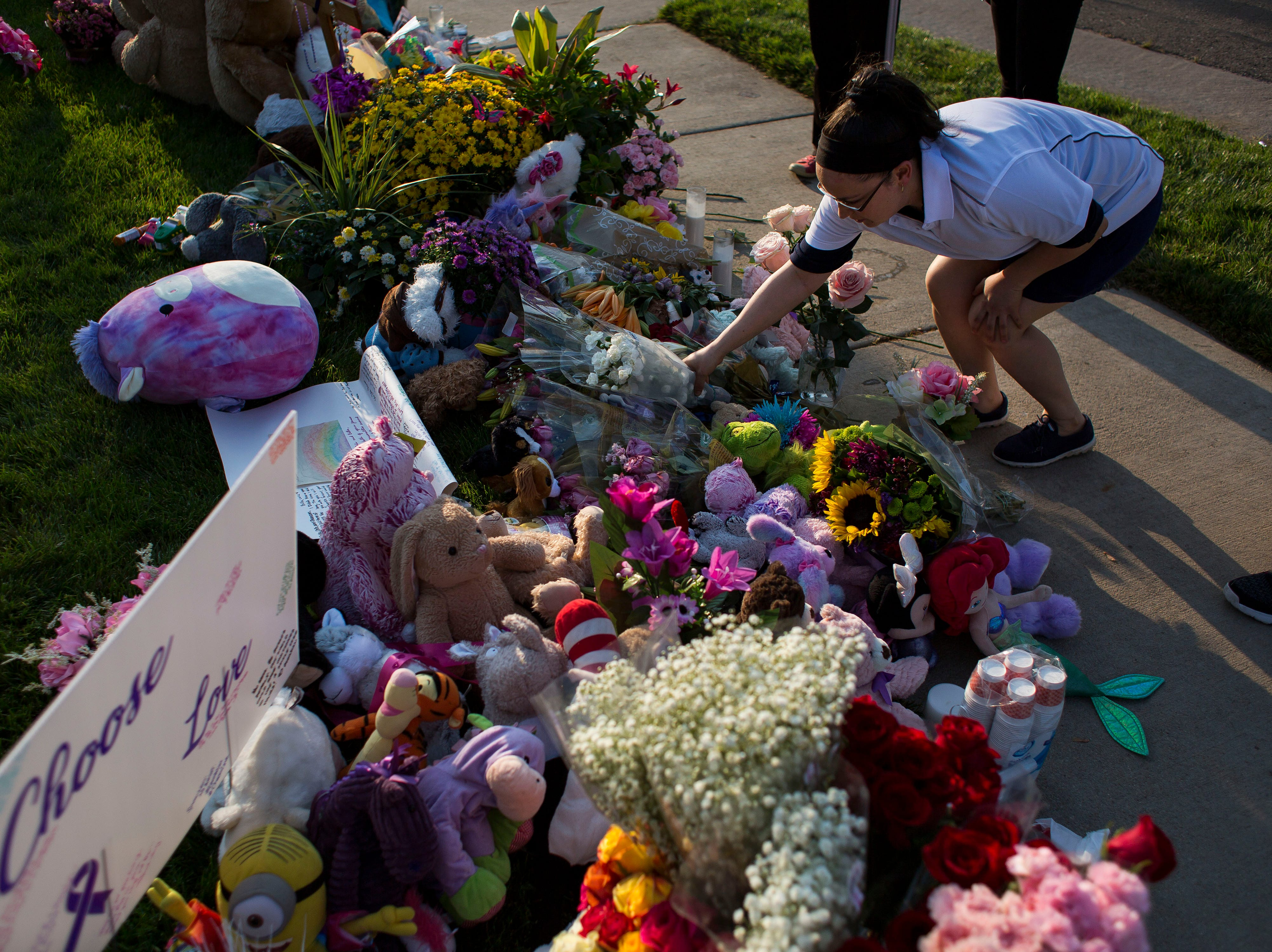 Yuliana Carmona places flowers at a memorial for a candle-lit vigil for the slain Shanann Watts and her two daughters, Bella, 4, and Celeste, 3, in front of the Watts' family home on Friday, Aug. 17, 2018, in Frederick, Colo.