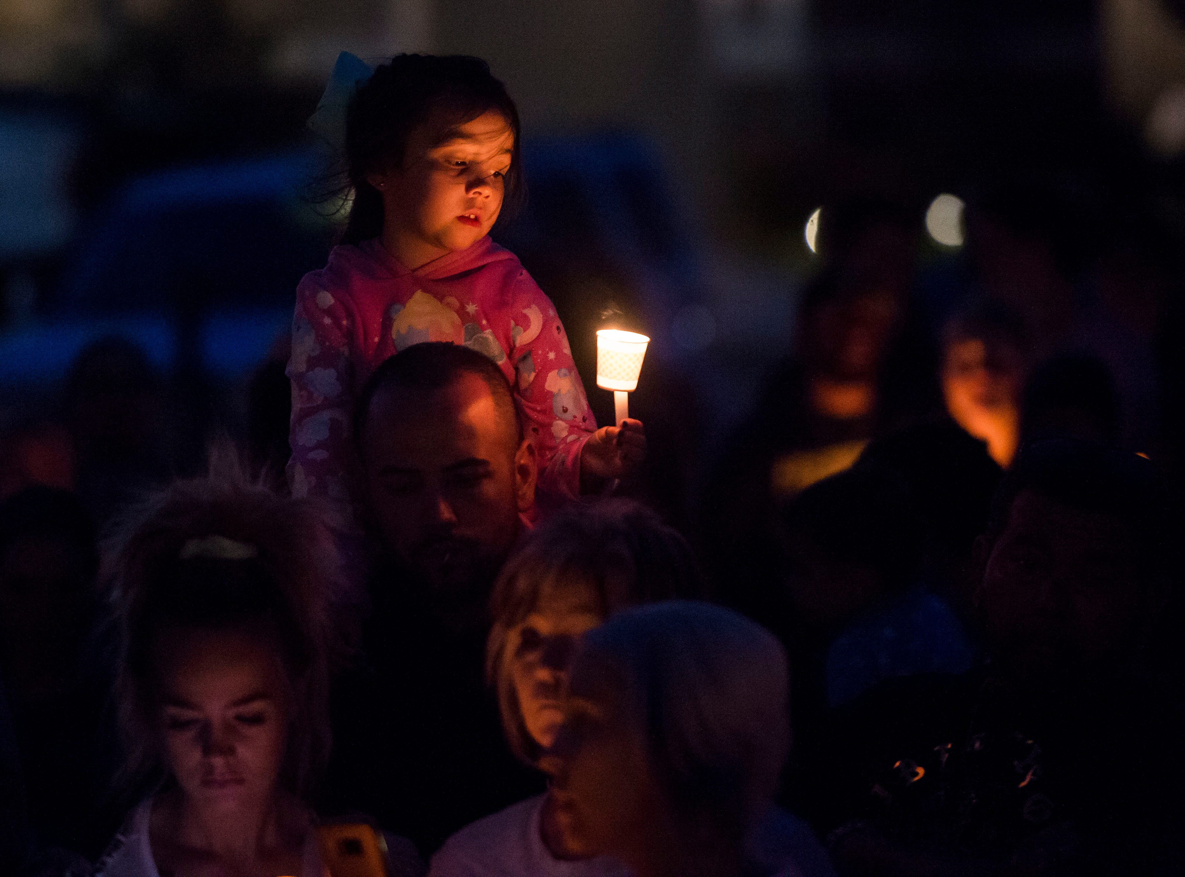 A young girl sits on an adults shoulders during a candle-lit vigil for the slain Shanann Watts and her two daughters, Bella, 4, and Celeste, 3, in front of the Watts' family home on Friday, Aug. 17, 2018, in Frederick, Colo.