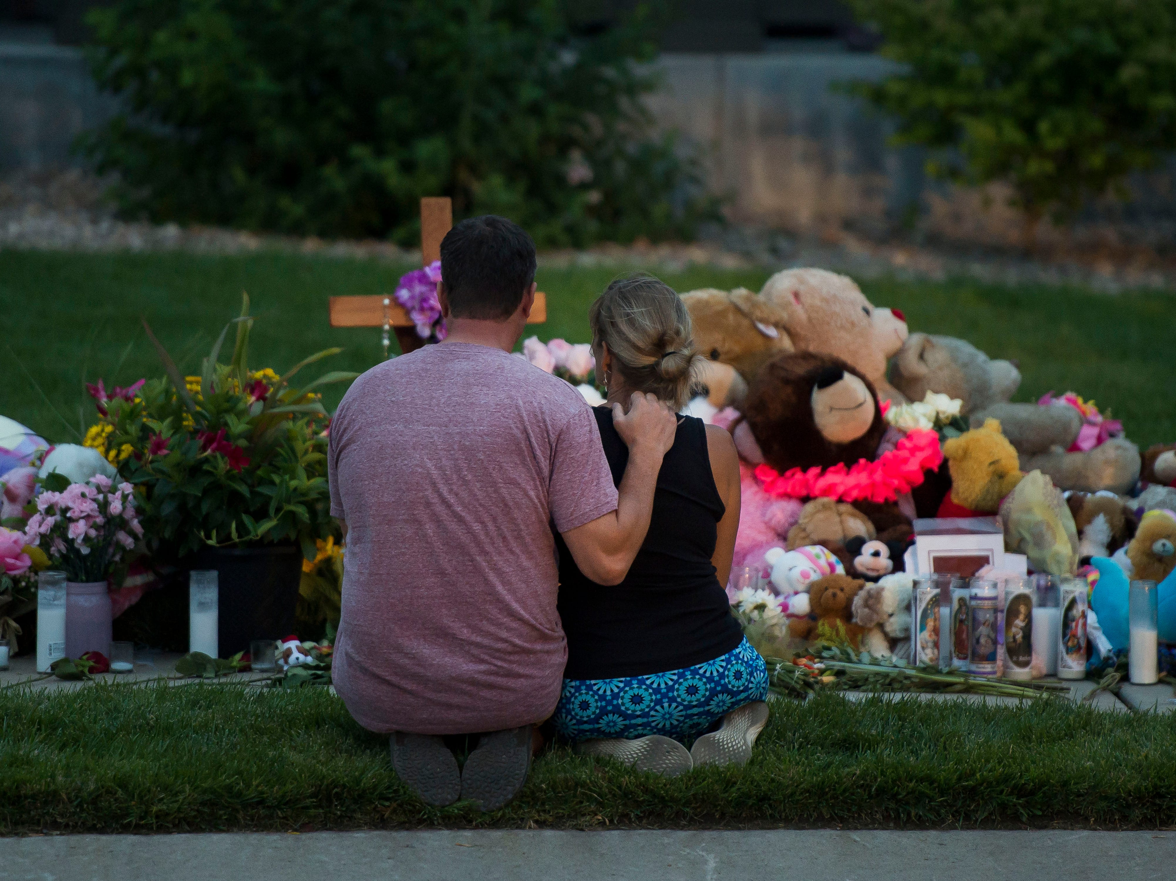 Jason and Diane Crookshank, from Erie, sit in front of a memorial before people gather for a candle-lit vigil for the slain Shanann Watts and her two daughters, Bella, 4, and Celeste, 3, in front of the Watts' family home on Friday, Aug. 17, 2018, in Frederick, Colo.