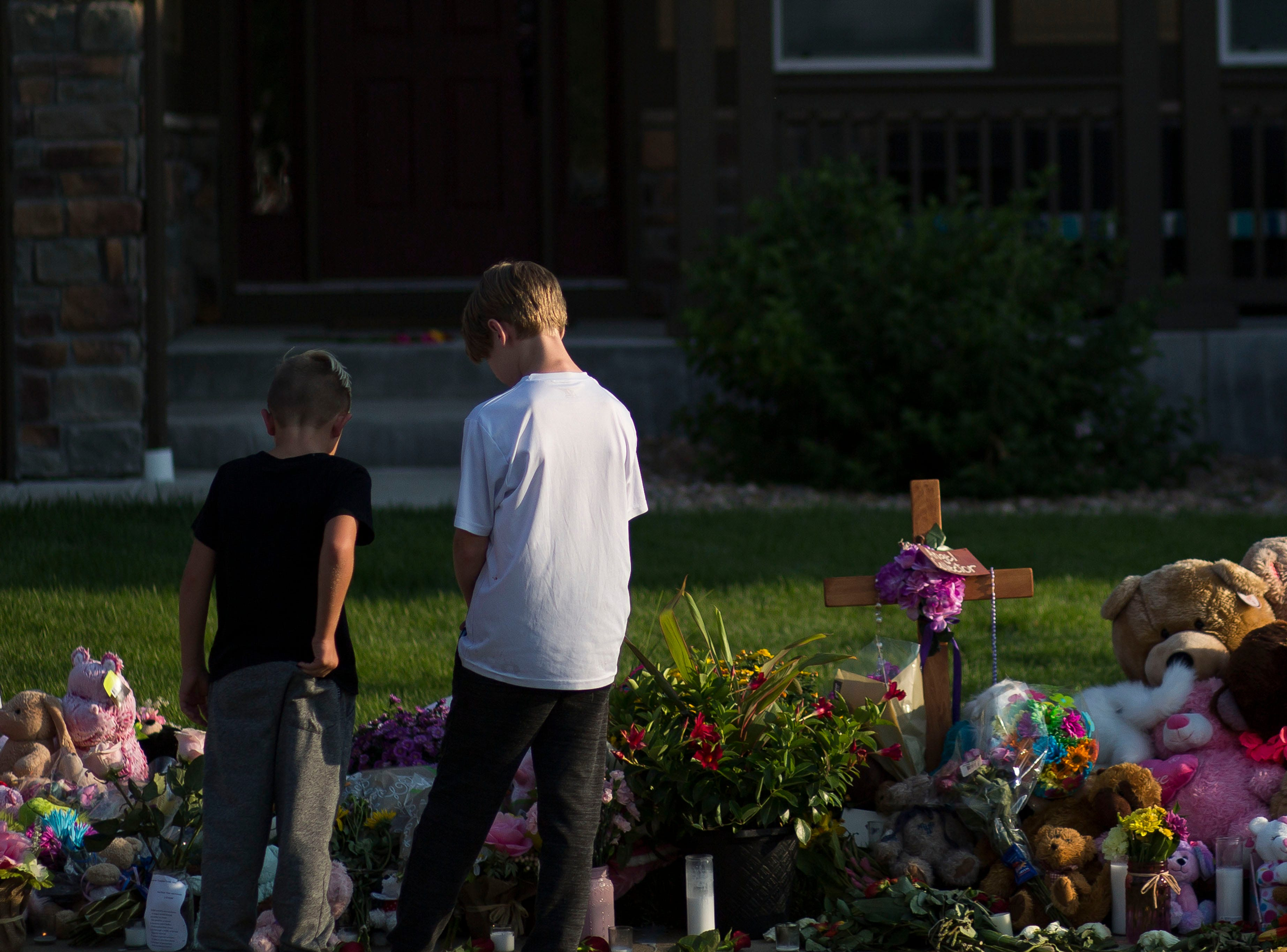 Two young boys look at a memorial for the slain Shanann Watts and her two daughters, Bella, 4, and Celeste, 3, in front of the Watts' family home on Friday, Aug. 17, 2018, in Frederick, Colo.