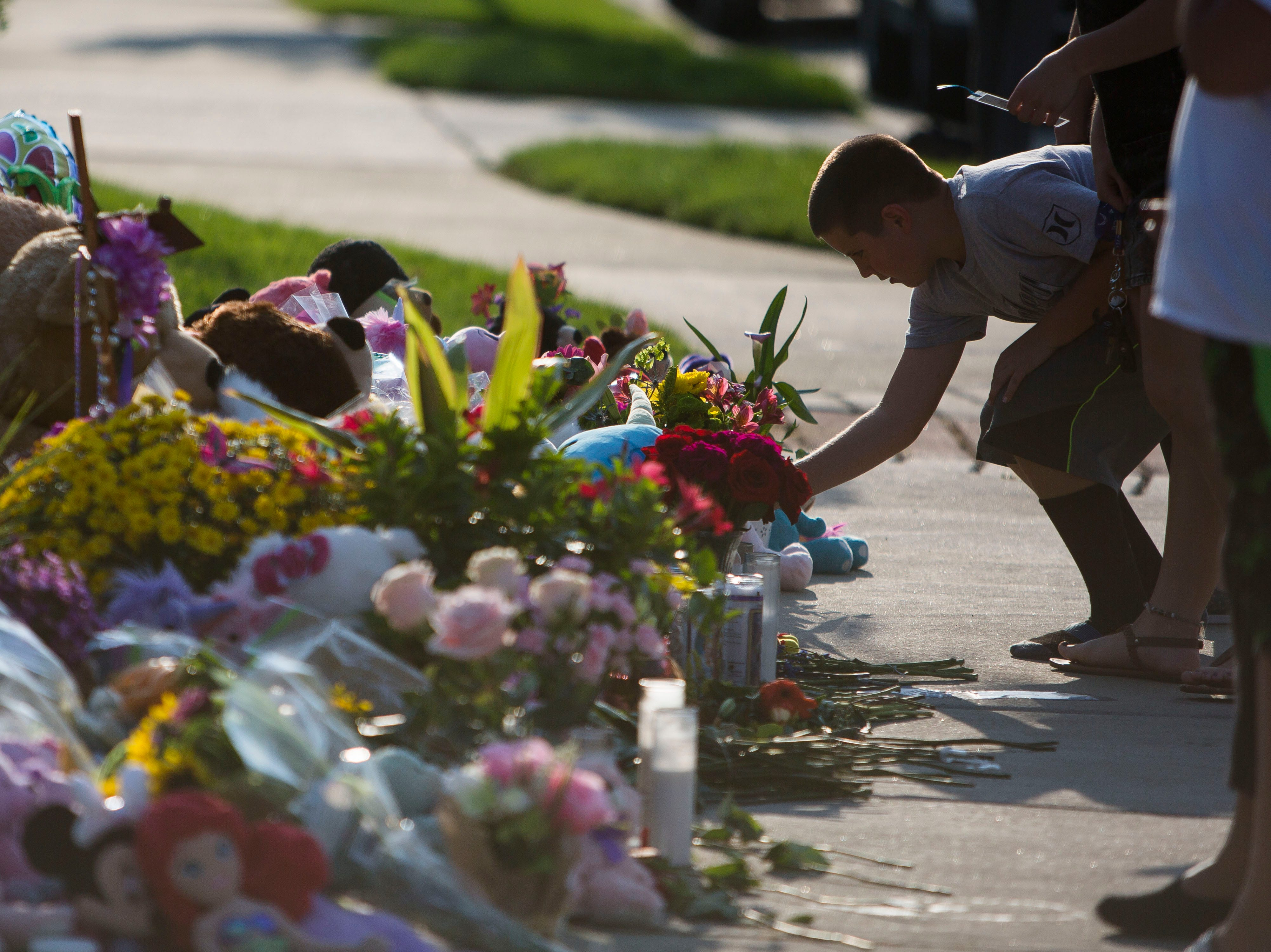 Frederick resident Brady Dwinal, 10, leans over a memorial of flowers, stuffed animals and hand-written notes for the slain Shanann Watts and her two daughters, Bella, 4, and Celeste, 3, in front of the Watts' family home on Friday, Aug. 17, 2018, in Frederick, Colo.