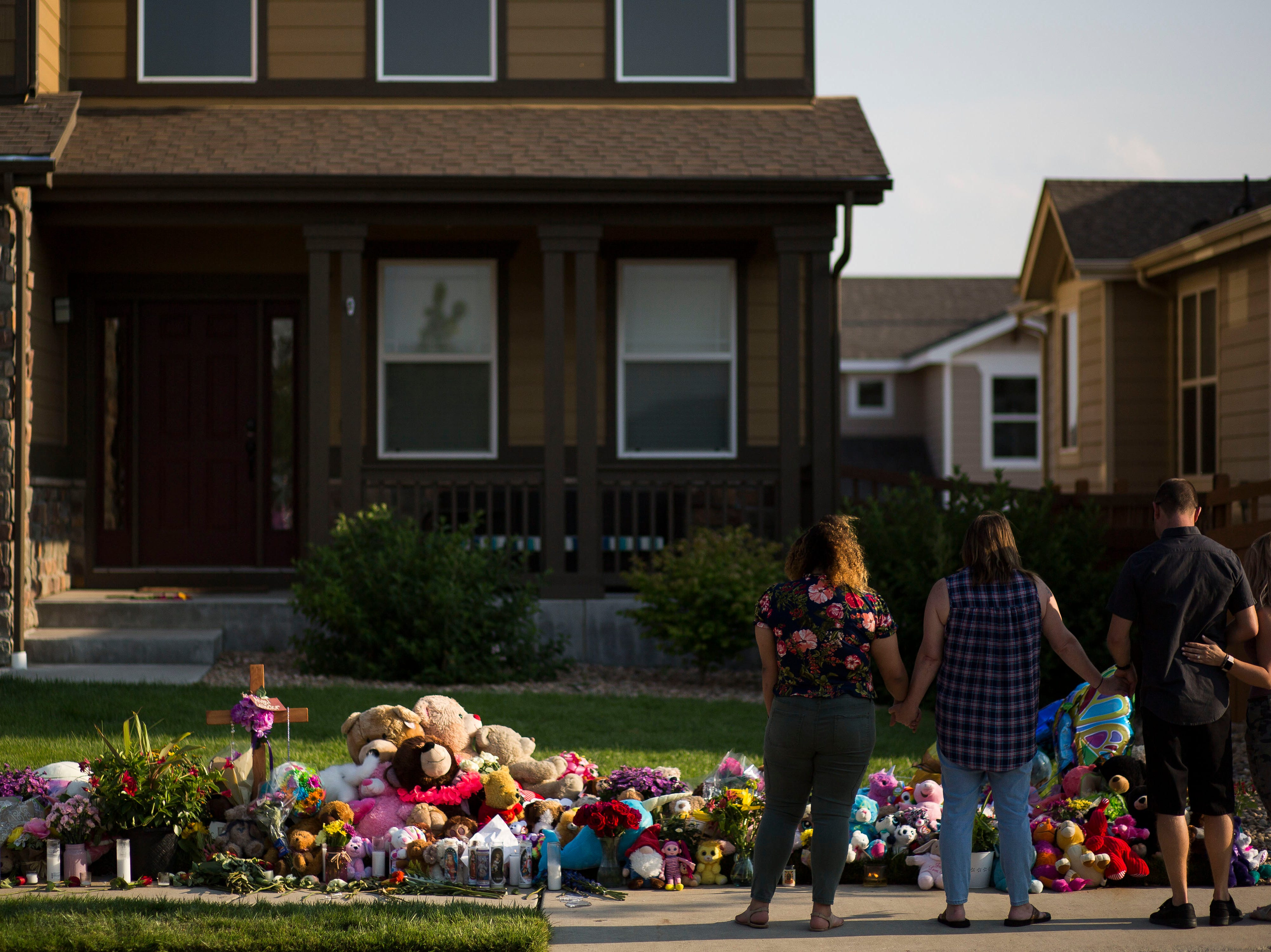 People gather at a memorial for the slain Shanann Watts and her two daughters, Bella, 4, and Celeste, 3, in front of the Watts' family home on Friday, Aug. 17, 2018, in Frederick, Colo.