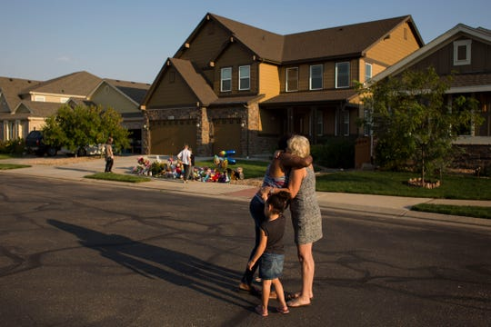 Firestone resident Jaba Wright, left, hugs neighborhood resident Mary Ann Bogner while holding the hands of her granddaughters Janaya, 4, and Maria, 3, in front of a memorial for the slain Shanann Watts and her two daughters, Bella, 4, and Celeste, 3, in front of the Watts' family home on Friday, Aug. 17, 2018, in Frederick, Colo.