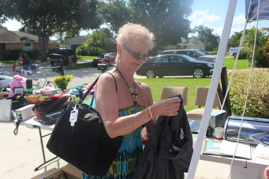 Fort Myers resident Carol Ryan checks out a shirt during a yard sale that was used as a fundraiser for Buckets of Hope.