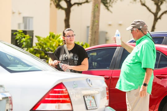 Martin gives directions to where the mailboxes are to a student after handing her water. President Mike Martin handed out water to students and parents as they are moving into to the residence halls on Friday. This is a ritual that reminds him why he does this job.