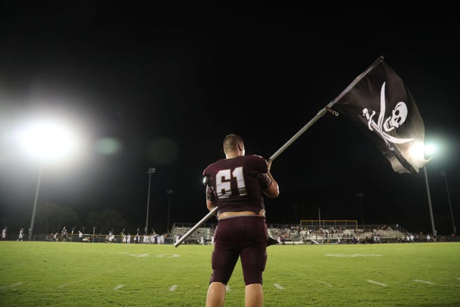 Riverdale's Thomas Barfield waves a Raiders flag before a preseason game against Cypress Lake on Friday, Aug. 17 at Riverdale High School.