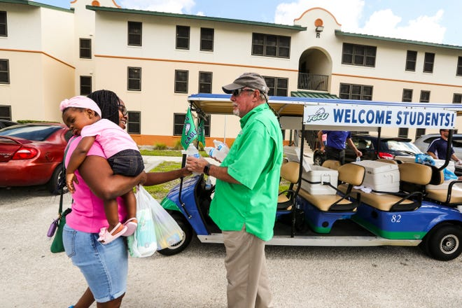 Martin hands water to a parent. FGCU President Mike Martin handed out water to students and parents as they are moving into to the residence halls on Friday. This is a ritual that reminds him why he does this job.