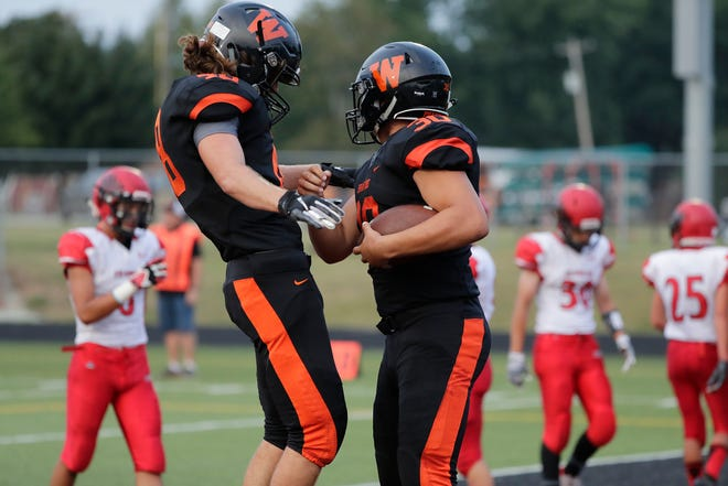 West De Pere's Cody Cavil (30) celebrates with Matt Kempen (48) after Cavil scored a touchdown against Shawano in a Bay Conference football game at West De Pere high school on Friday, August 17, 2018 in De Pere, Wis.