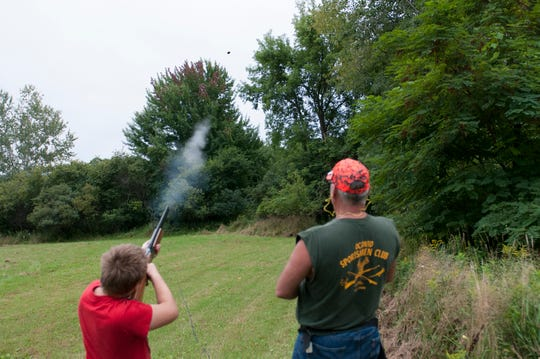 Accompanied by an Oconto Sportsman's Club member, a youth fires a shotgun at a clay target during last year's Youth Outdoor Day, which is this year is Saturday, Aug. 25