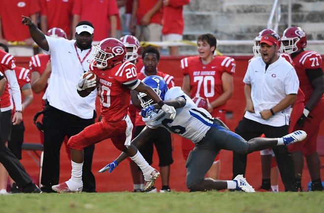 Greenville's Collin Wakefield (20) returns a kick past Woodmont's Tobias Jones (6) Friday, August 17, 2018 at Sirrine Stadium in Greenville.