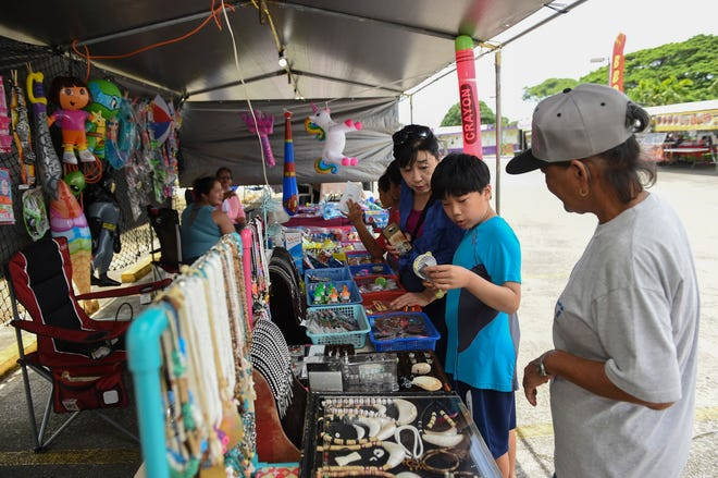 Event goers browse the toy selection at Aguigui's booth during the second annual Santa Rosa Fiesta Carnival in Agat on Aug. 18, 2018.