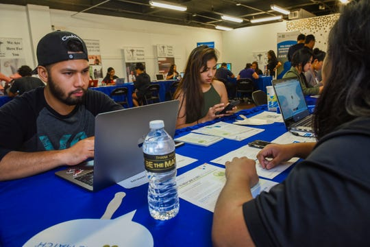 Rico Diaz, left, and his girlfriend Jenn Espinoza, use a laptop and a mobile phone to input information during a bone marrow drive at the Agana Shopping Center on Saturday, Aug. 18, 2018. The drive, hosted by the Guam Medical Association, was held to search for compatible donors to benefit Diaz's niece, Imani Malanche.