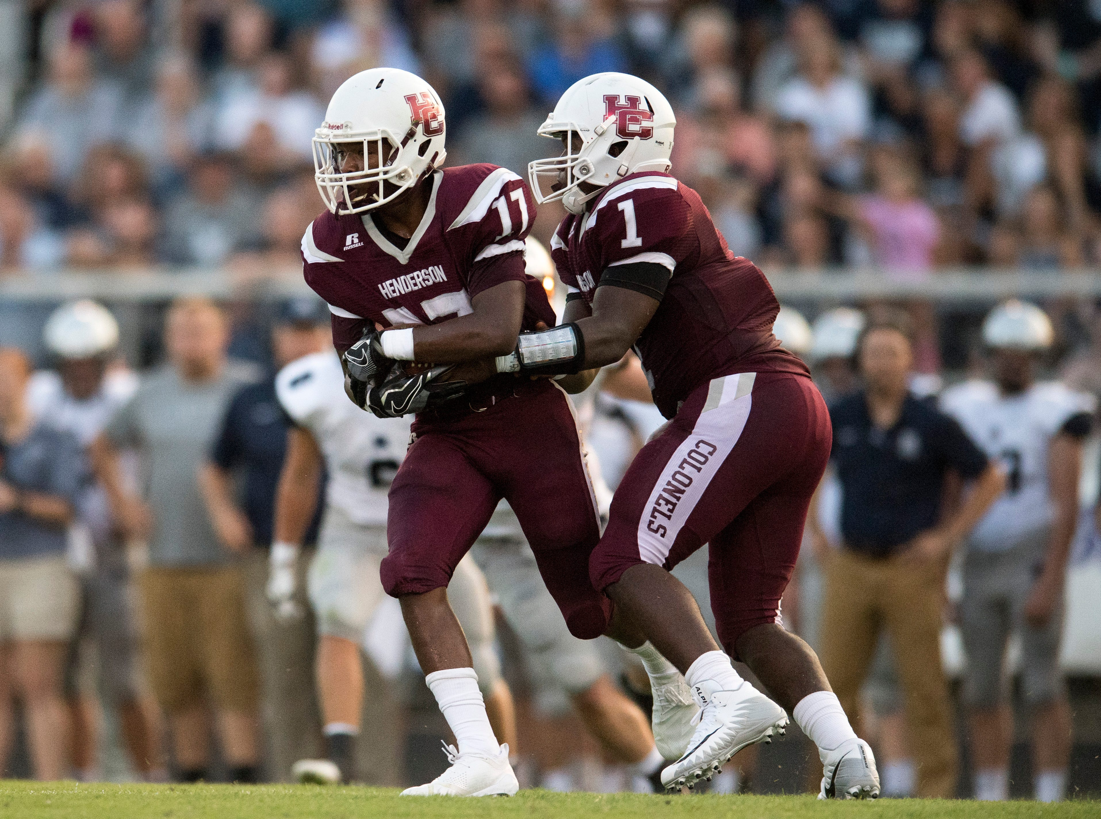 Henderson's Skip Patterson (1)  hands the ball to HendersonÕs Isaiah Easley (17) during Reitz vs Henderson County game at Colonel Stadium Friday, August 17, 2018. The Panthers defeated the Colonels 41-35 in the season opening game.