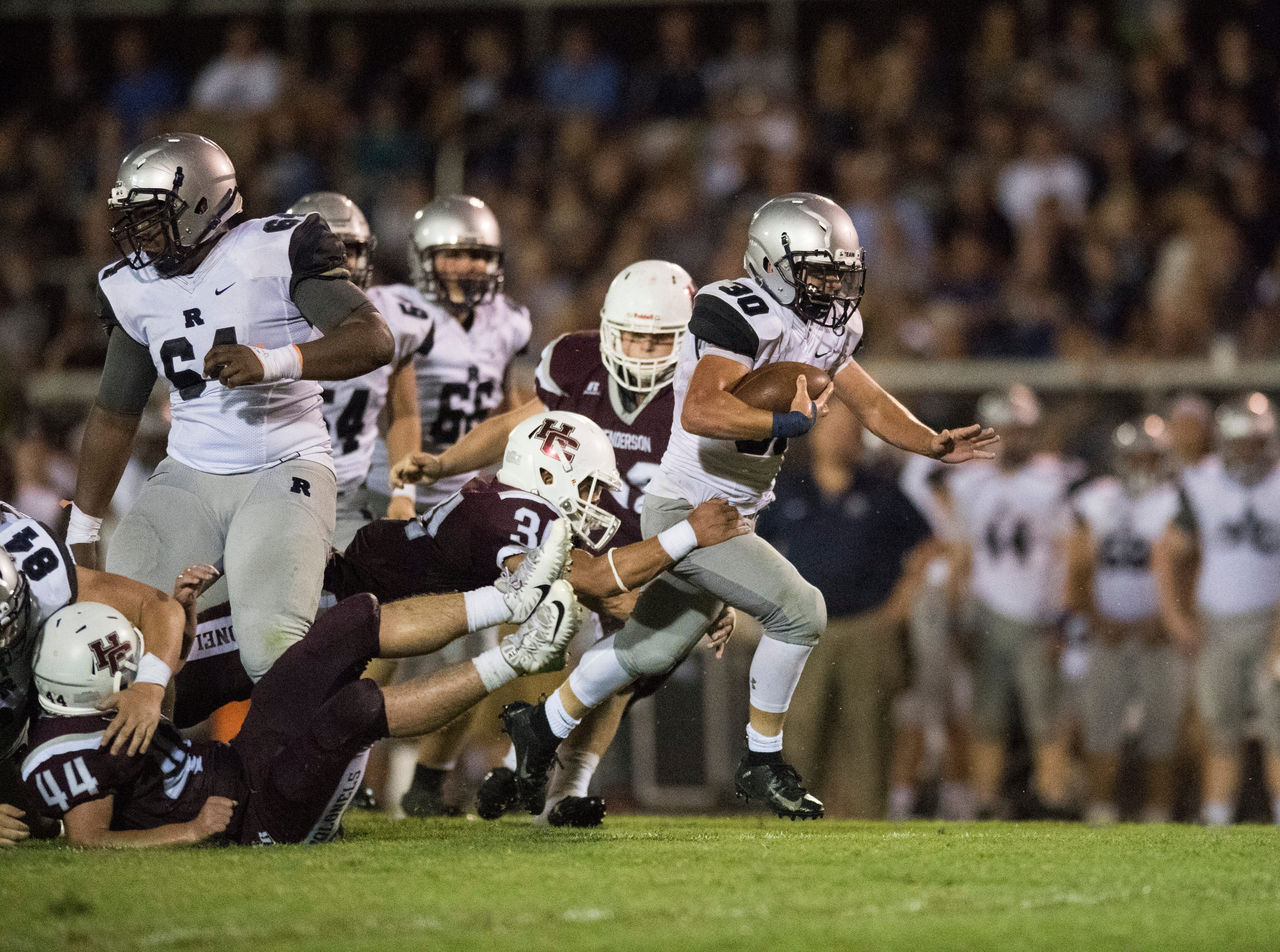 Reitz's Alex Mitchell (30) breaks through the Henderson Colonels defensive line during the Reitz vs Henderson County game at Colonel Stadium Friday, August 17, 2018. The Panthers defeated the Colonels 41-35 in the season opening game.