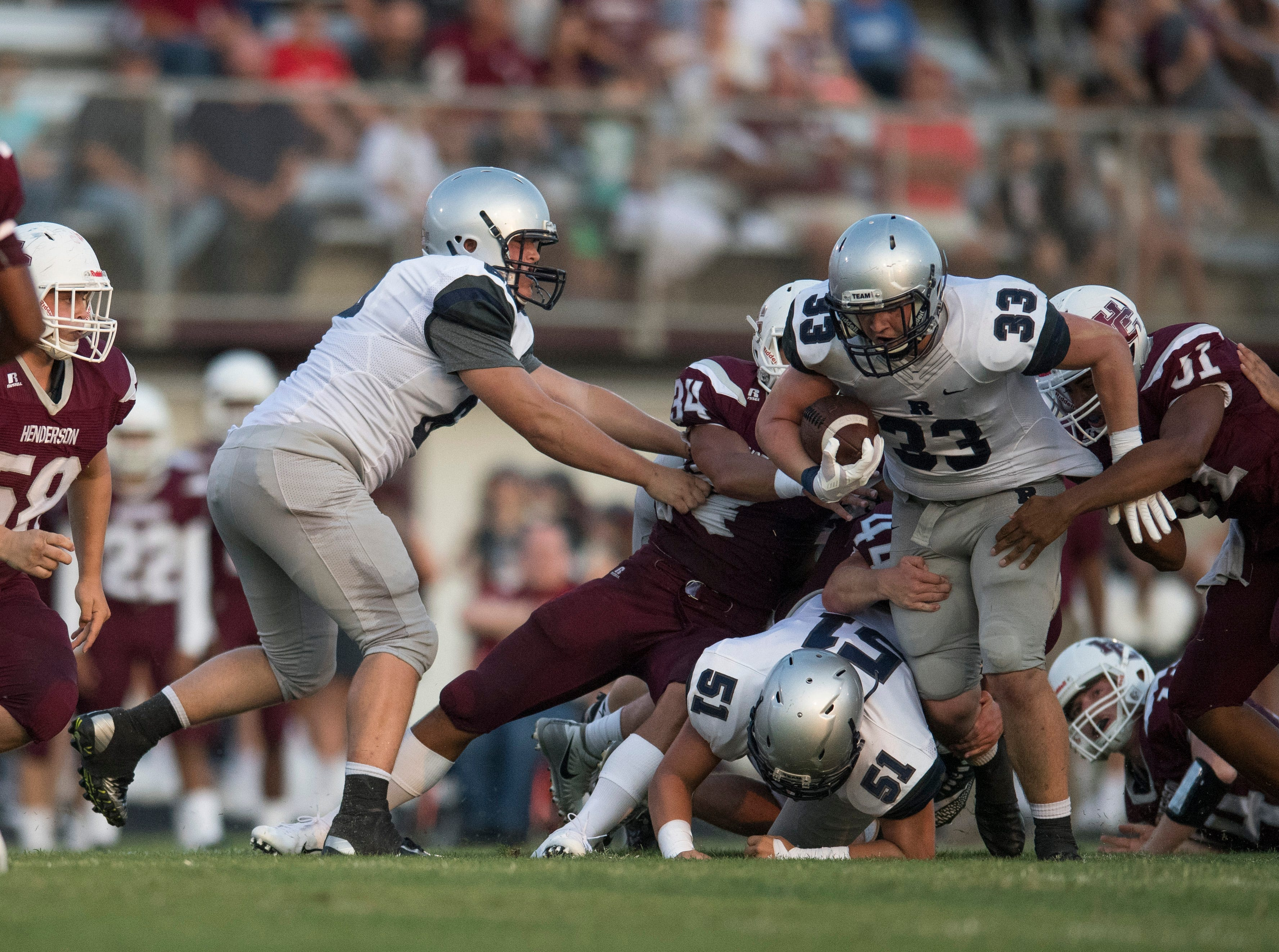 Reitz's Carter Schnarr (33) is tackled by Henderson County defense during the Reitz vs Henderson County game at Colonel Stadium Friday, August 17, 2018. The Panthers defeated the Colonels 41-35 in the season opening game.