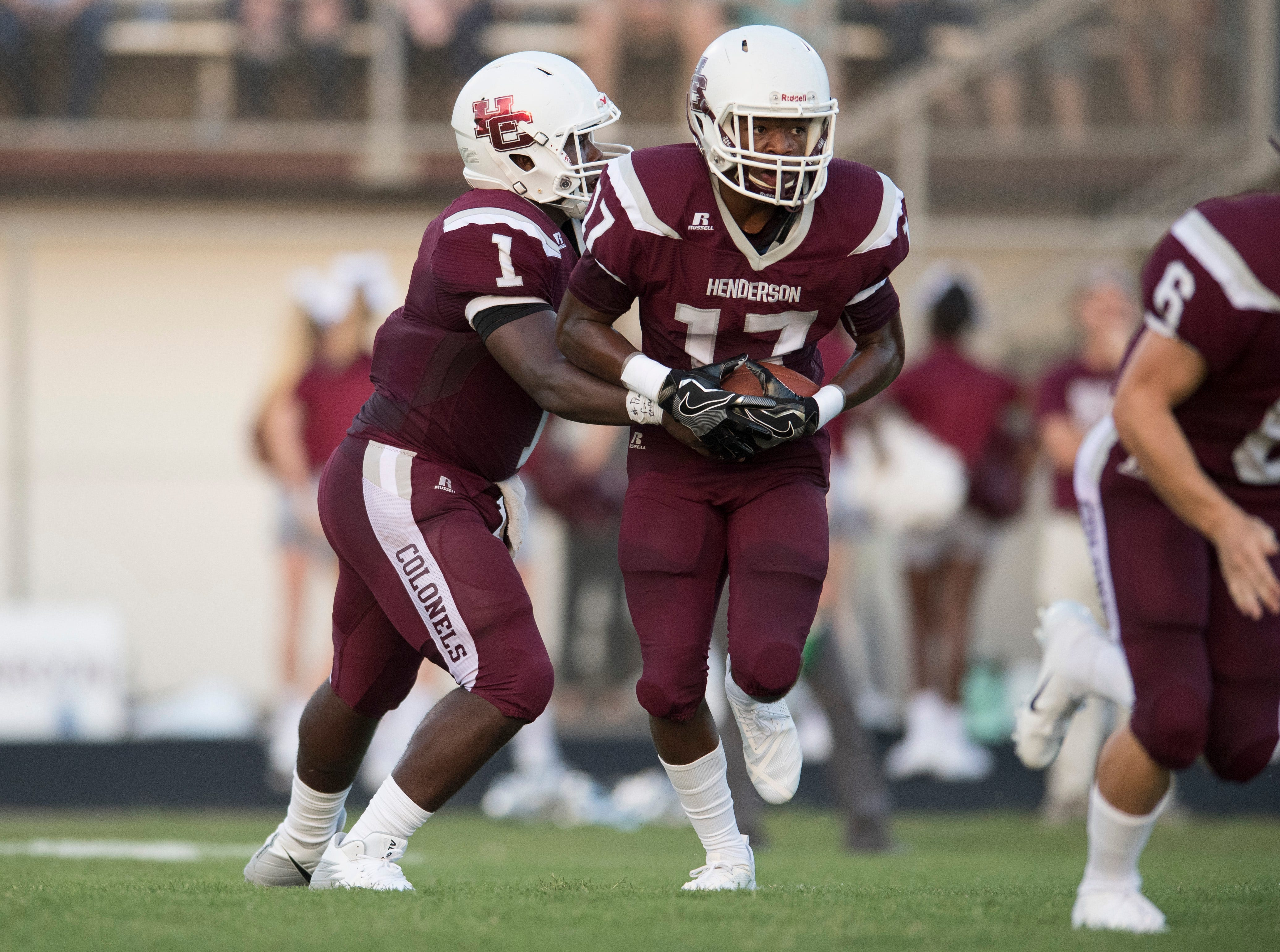 Henderson's Skip Patterson (1)  hands off the ball to HendersonÕs Isaiah Easley (17) during the Reitz vs Henderson County football game Colonels Stadium Friday, August 17, 2018.  The Panthers defeated the Colonels 41-35 in the season opening game.