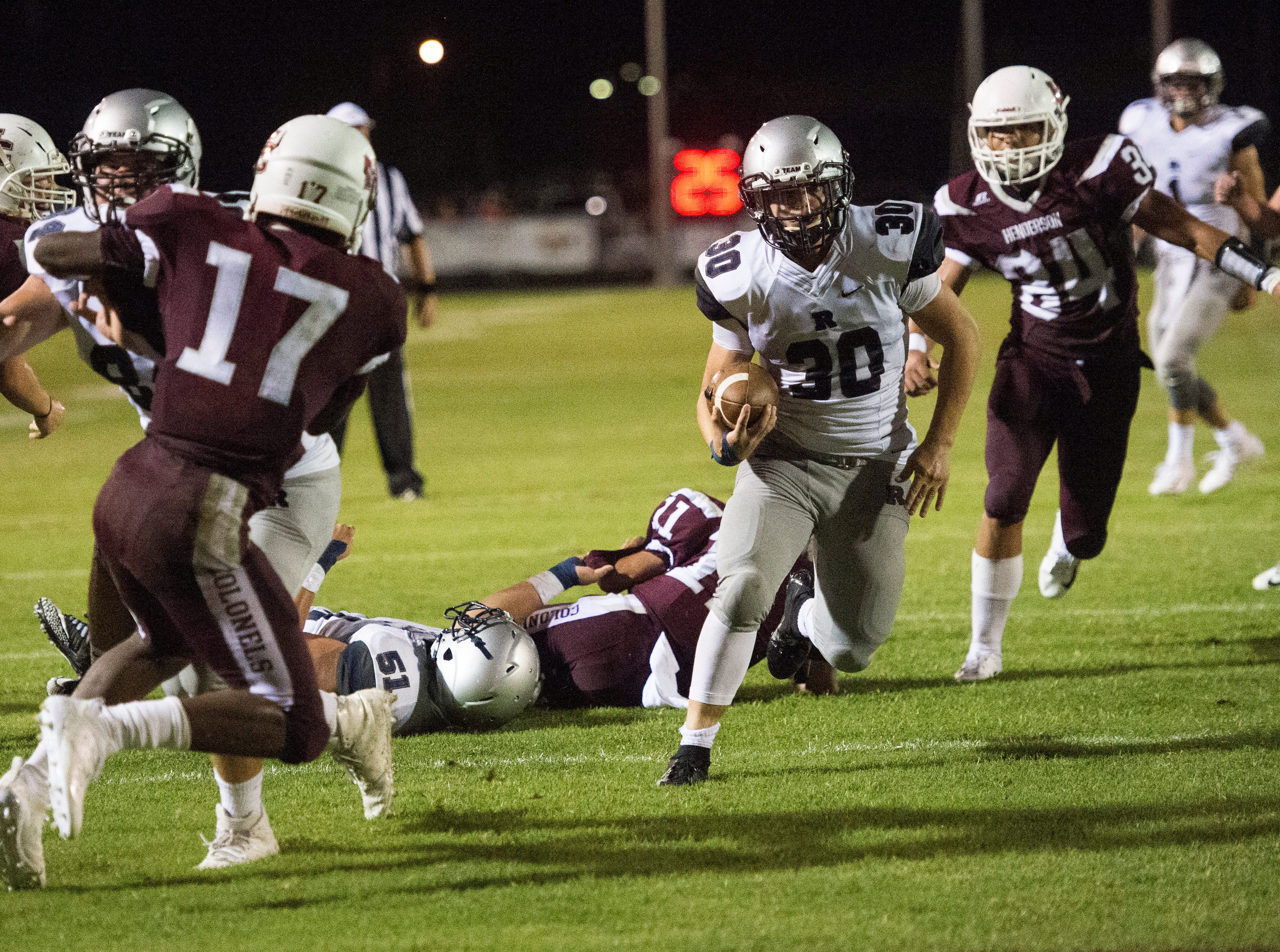 Reitz's Alex Mitchell (30) runs the ball though an opening during the Reitz vs Henderson County game at Colonel Stadium Friday, August 17, 2018. The Panthers defeated the Colonels 41-35 in the season opening game.