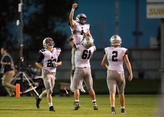 Reitz's Jarrett Naas (61) holds up  Quarterback Eli Wiethop (1) after while celebrating a touchdown made by Wiethop during the Reitz vs Henderson County game at Colonel Stadium Friday, August 17, 2018. The Panthers defeated the Colonels 41-35 in the season opening game.
