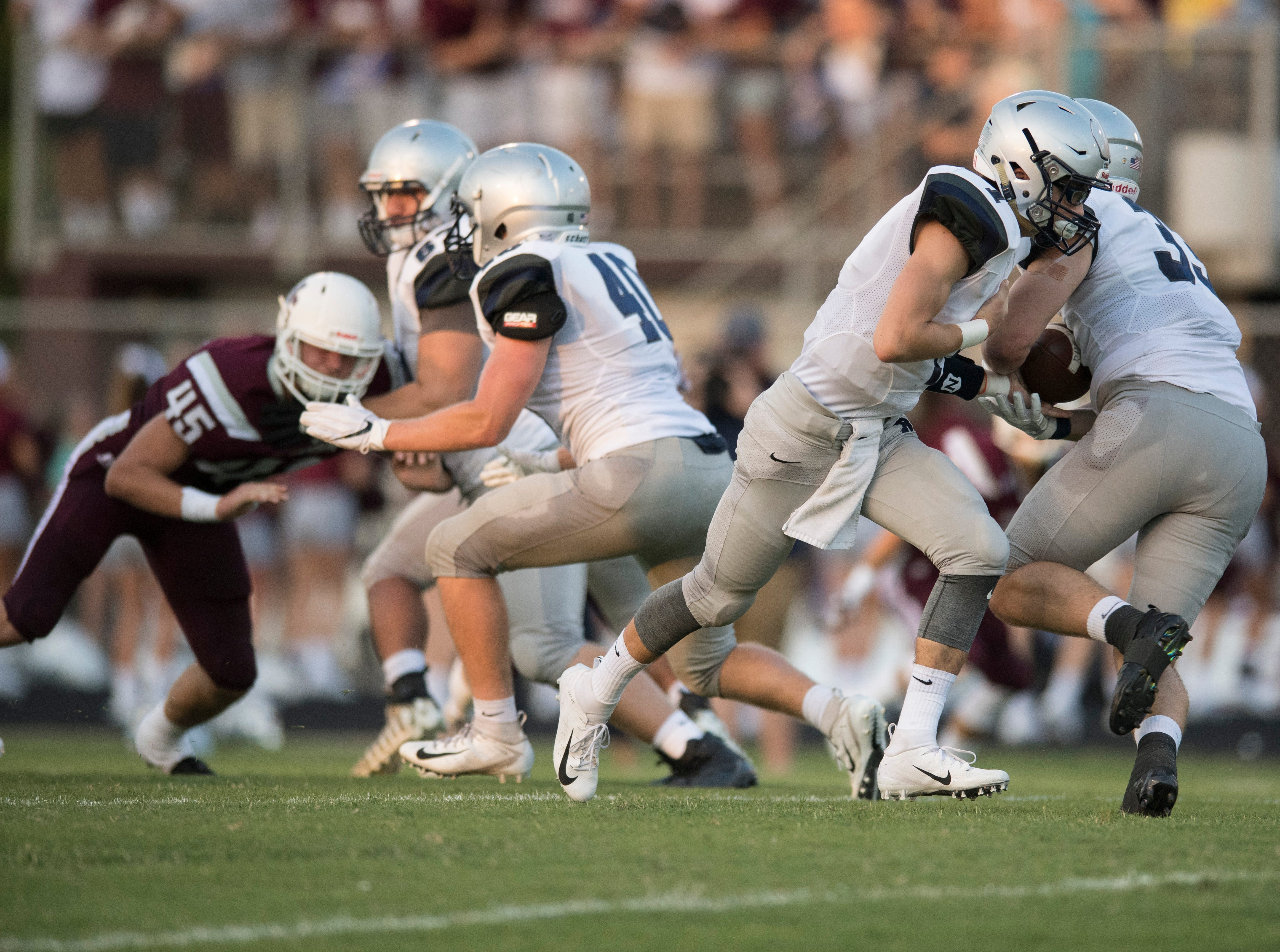 Reitz's Quarterback Eli Wiethop (1)  hands the ball to Reitz's Carter Schnarr (33) during the first quarter of the Reitz vs Henderson County game at Colonel Stadium Friday, August 17, 2018. The Panthers defeated the Colonels 41-35 in the season opening game.