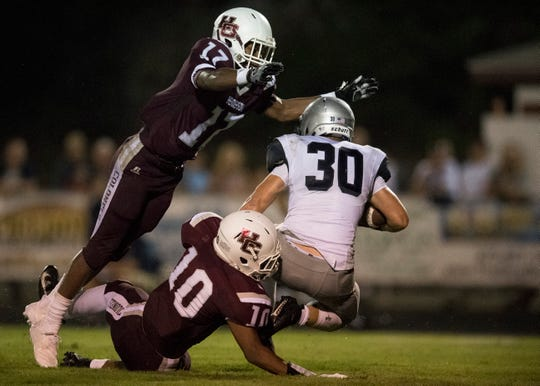 Henderson's Isaiah Easley (17)leaps in the air while HendersonÕs Daymian Dixon (10)  tackles Reitz's Alex Mitchell (30) during the Reitz vs Henderson County game at Colonel Stadium Friday, August 17, 2018. The Panthers defeated the Colonels 41-35 in the season opening game.
