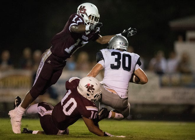 Henderson's Isaiah Easley (17)leaps in the air while Henderson's Daymian Dixon (10) tackles Reitz's Alex Mitchell (30) during the Reitz vs Henderson County game at Colonel Stadium Friday, August 17, 2018. The Panthers defeated the Colonels 41-35 in the season opening game.