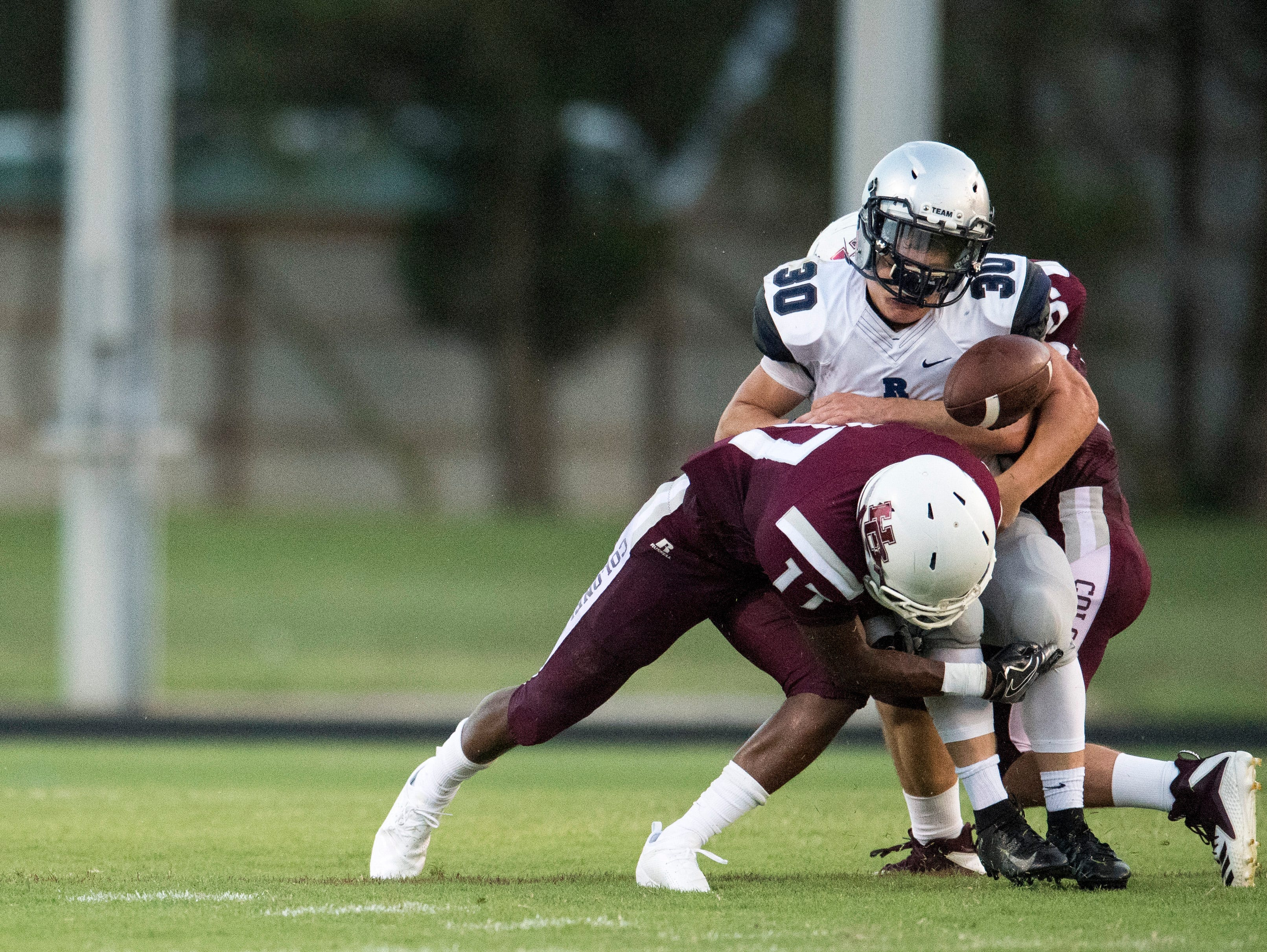 The Henderson Colonels Isaiah Easley (17) tackles Reitz's Alex Mitchell (30) causing Mitchell to loose the ball during the Reitz vs Henderson County game at Colonel Stadium Friday, August 17, 2018. The Panthers defeated the Colonels 41-35 in the season opening game.