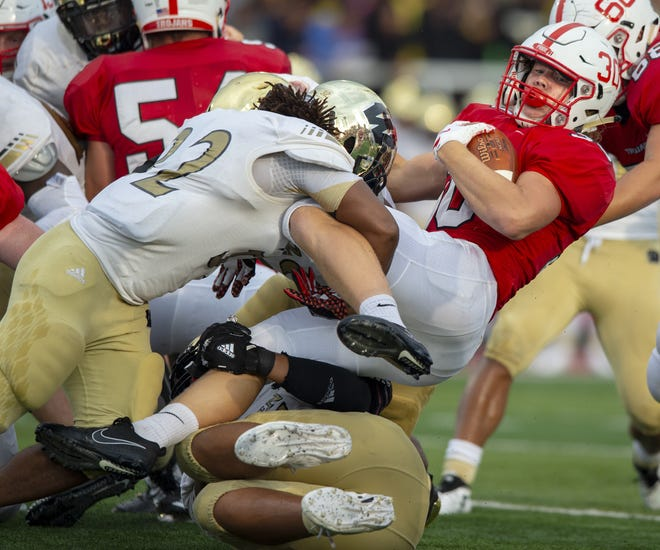 Center Grove High School sophomore Carson Steele (30) is hit by Warren Central High School senior Anthony Williams (22) during the first half of action. Center Grove High School hosted Warren Central High School in IHSAA varsity football action, Friday, Aug. 17, 2018.