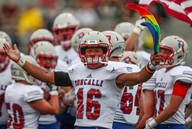 Roncalli Rebels running back Elijah Mahan (46) waves a pride flag as the team enters the field before kickoff against the Southport Cardinals at Southport High School on Friday, Aug. 17, 2018.