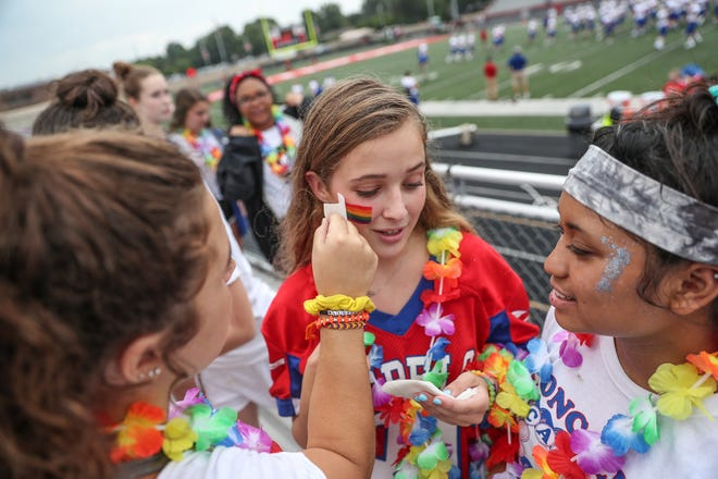 "Reagan O'Gara, a Roncalli senior, has a friend put a pride flag tattoo on her cheek before the Rebels' first football game of the season against the Southport Cardinals at Southport High School on Friday, Aug. 17, 2018. ""We're supporting Ms. Fitzgerald,"" she said. ""We're definitely trying to spread the news."""