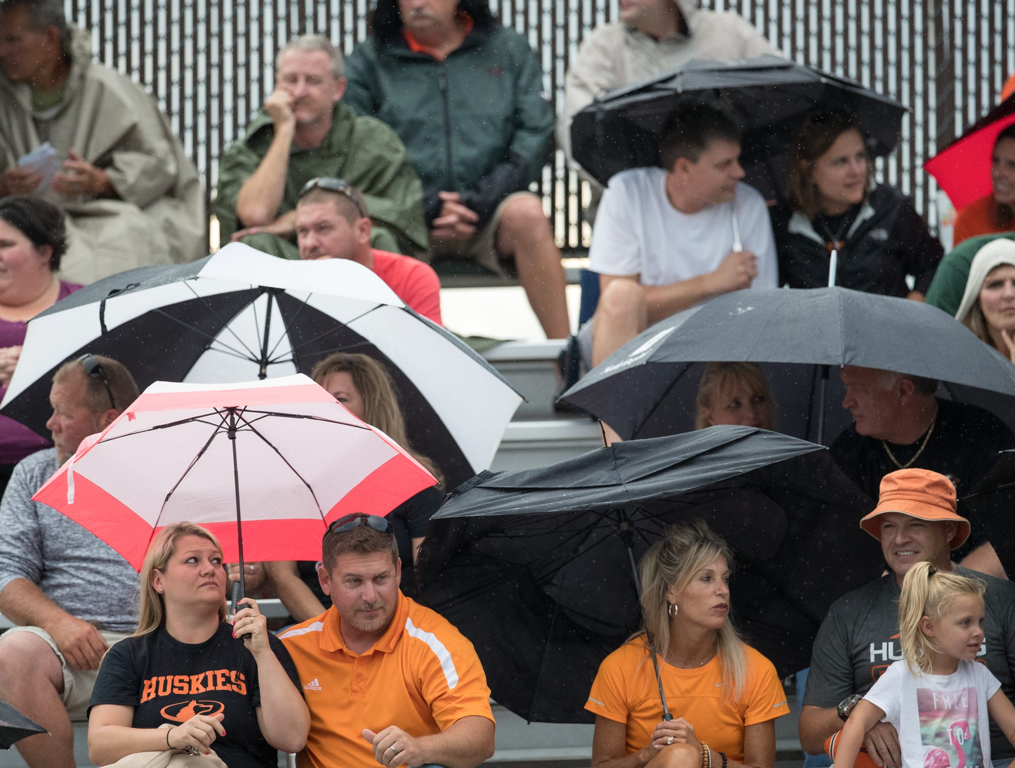 Fans duck under umbrellas during a brief first quarter shower, Mount Vernon High School at Hamilton Heights High School football, won by MVHS, 43-14, Arcadia, Friday, Aug. 17, 2018. This game is the first for HHHS head coach Jon Kirschner, who faced his father Mike Kirschner, a veteran and champion coach in his first season at MVHS.