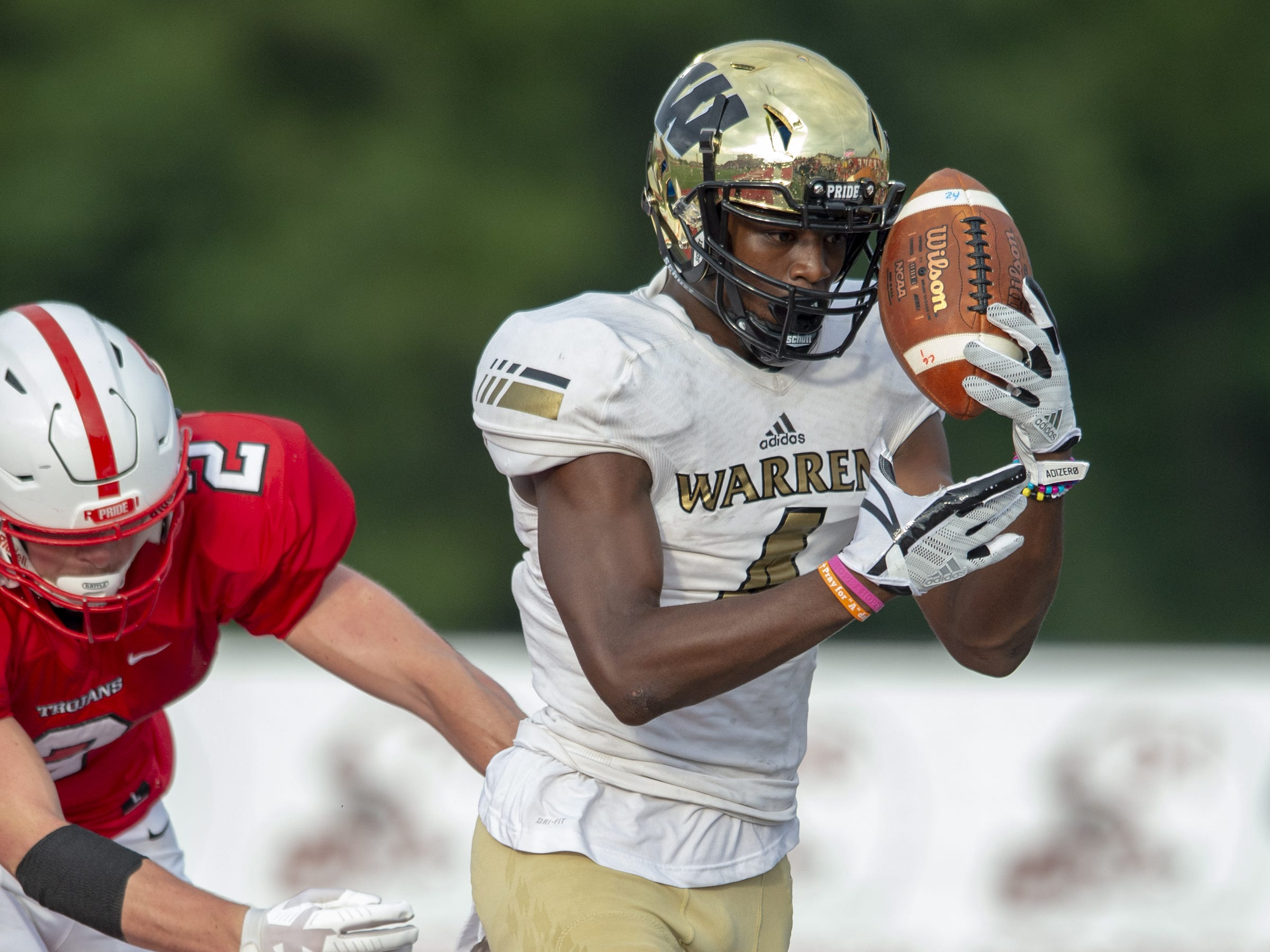 Warren Central High School senior David Bell (4) tries to gain control of the ball he intercepted in the back of the end zone before stepping out-of-bounds during the first half of action. Center Grove High School hosted Warren Central High School in IHSAA varsity football action, Friday, Aug. 17, 2018.