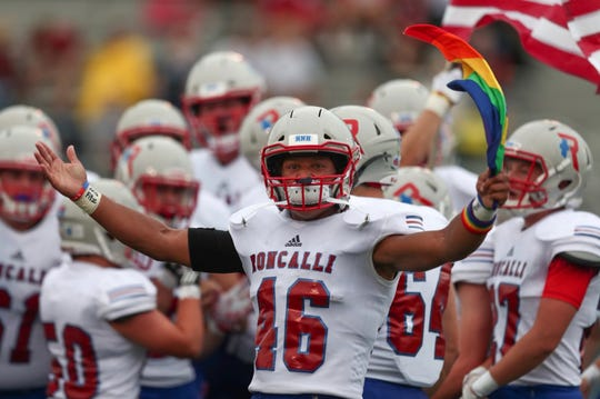 Roncalli running back Elijah Mahan carries a pride flag onto the field for their first game of the season against Southport.
