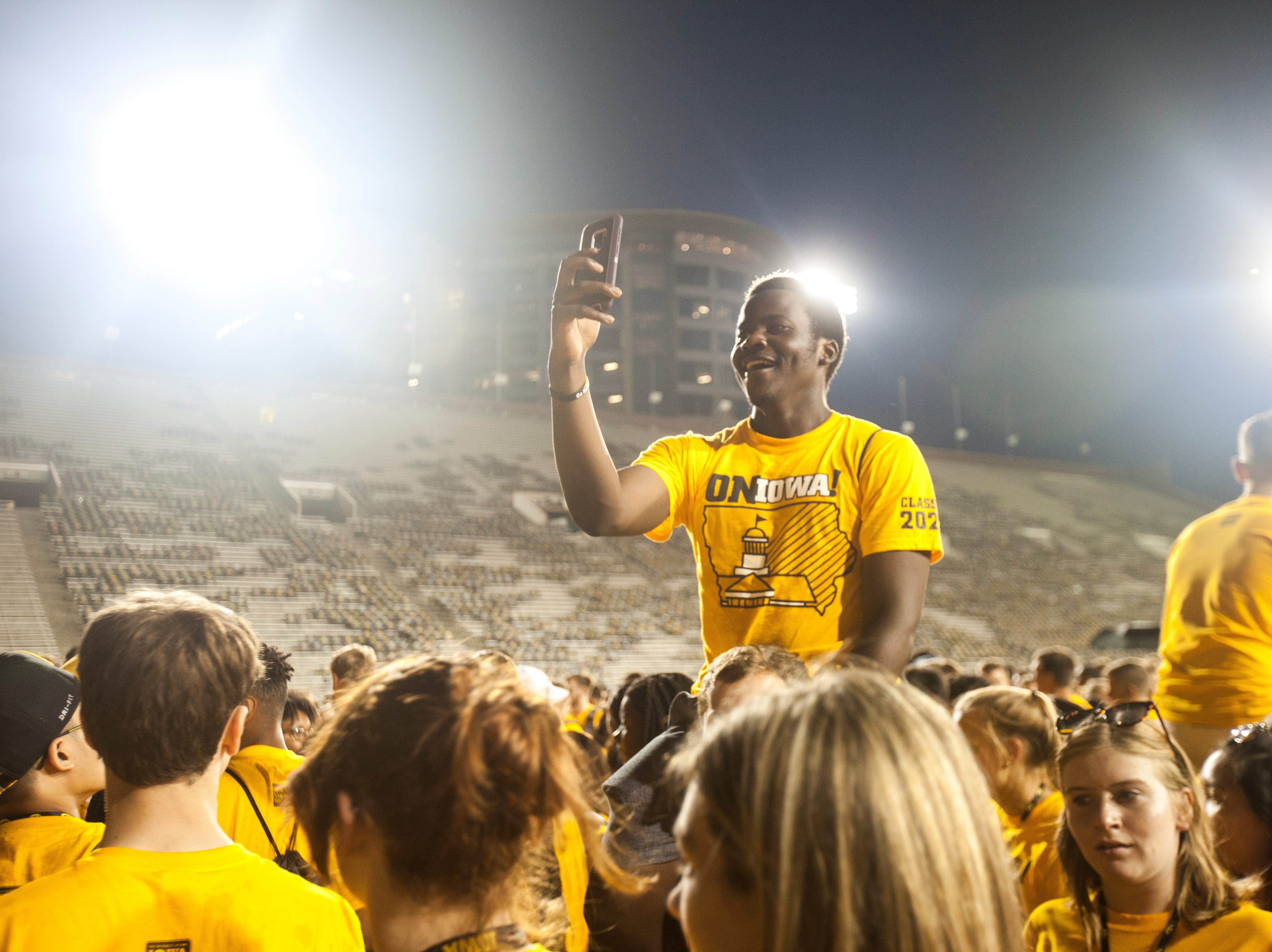 "Joseph Bentley, of Waterloo, Iowa, carries Elias ""Nami"" Mpundu, of Zambia, Africa, while students gather during an OnIowa event on Friday, Aug. 17, 2018, at Kinnick Stadium in Iowa City. Bentley is studying biology and Mpundu is studying human physiology."