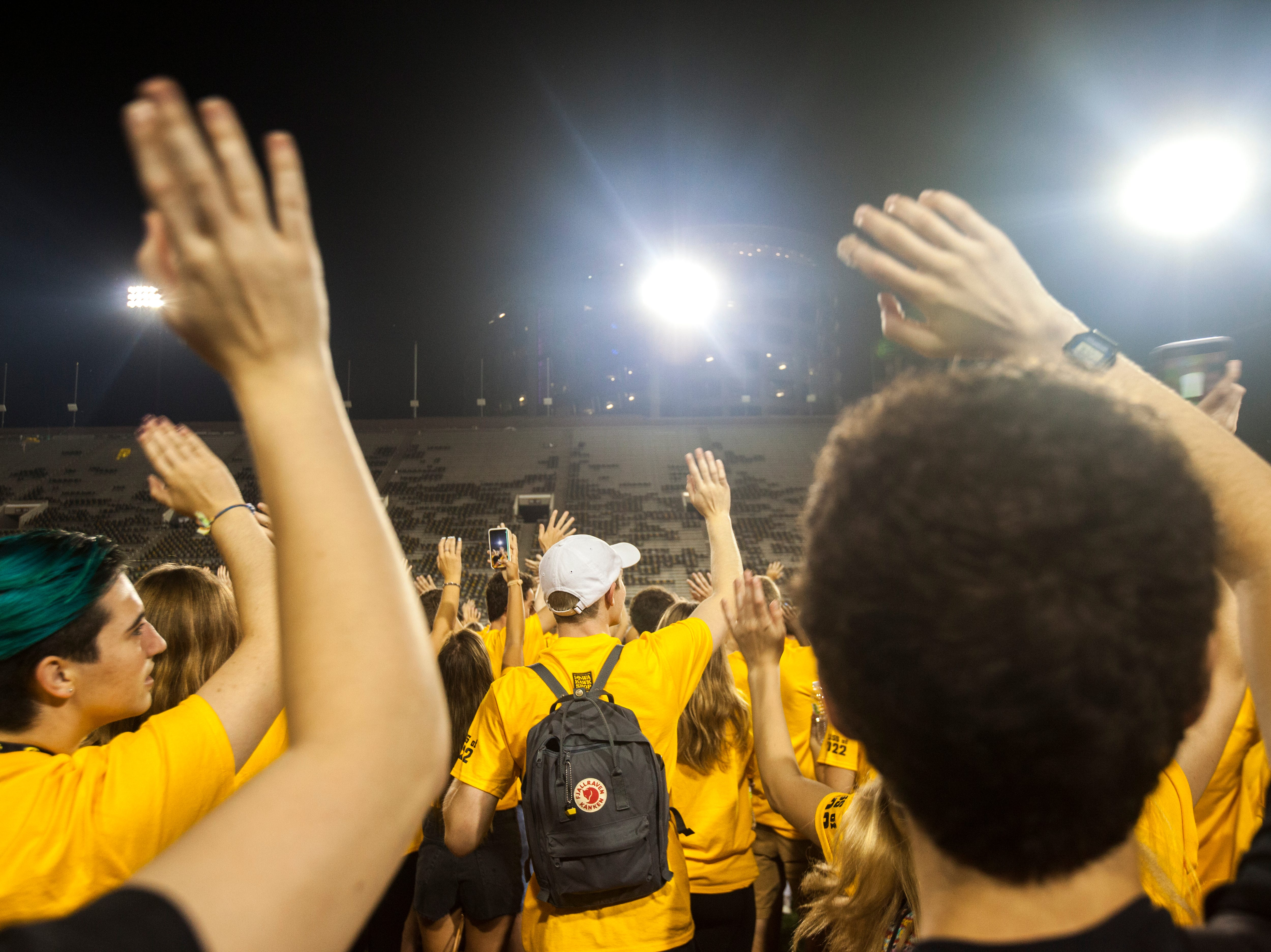 University of Iowa students wave towards people in the Stead Family Children's Hospital during an OnIowa event on Friday, Aug. 17, 2018, at Kinnick Stadium in Iowa City. The annual Kickoff at Kinnick allows new students a chance to walk on the field for their class photo.