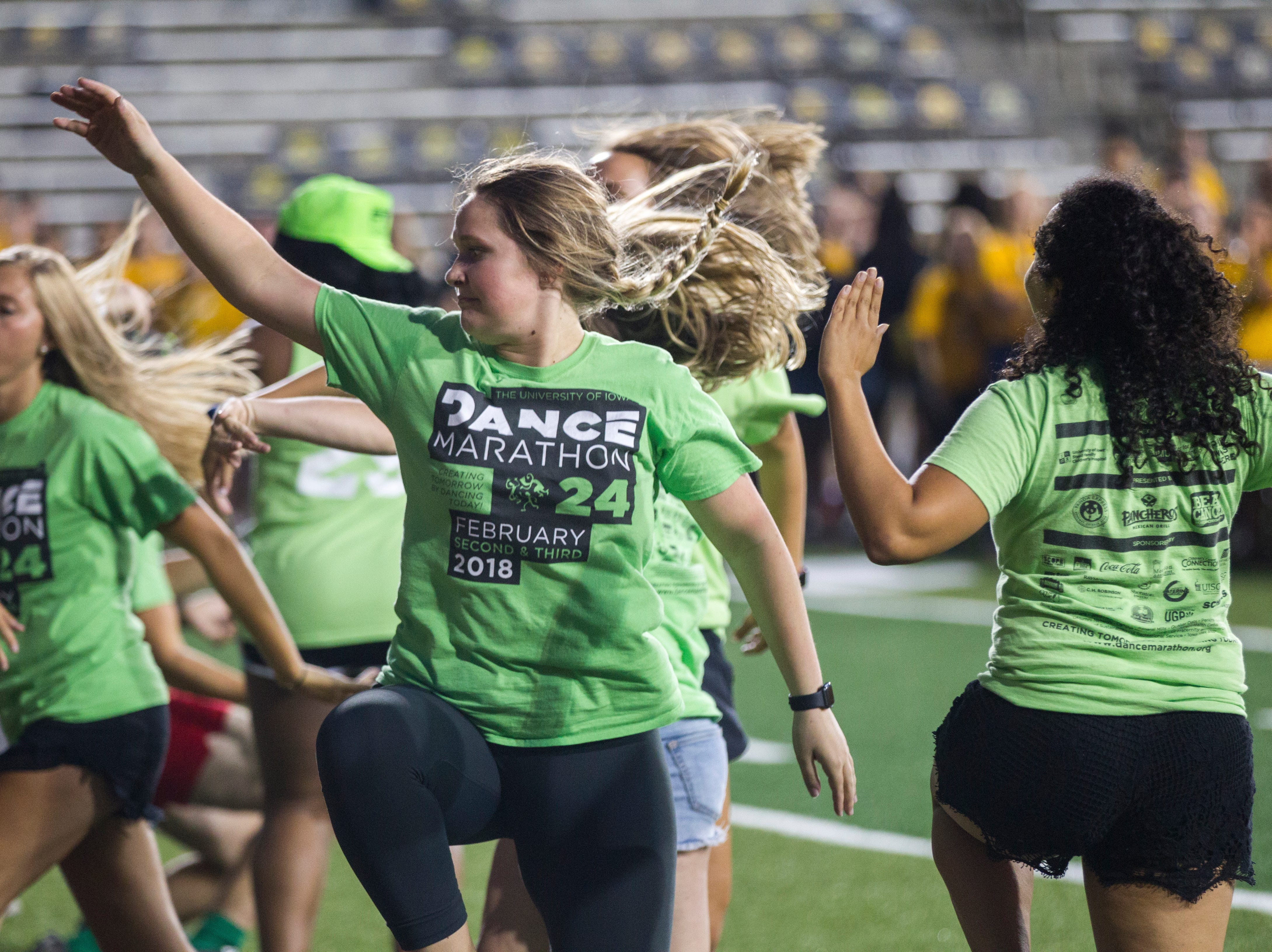 Amy Isebrand, of Le Mars, Iowa, dances with other members of Dance Maraton during an OnIowa event on Friday, Aug. 17, 2018, at Kinnick Stadium in Iowa City. The annual Kickoff at Kinnick allows new students a chance to walk on the field for their class photo.
