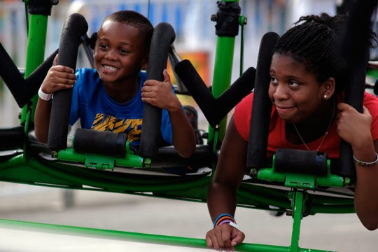 Fair attendees Kenneth Simon, 5, and Gari Miller prepare to ride a hang glider ride during the 2014 Tennessee Valley Fair in Knoxville, Tenn., on Friday, September 5, 2014.