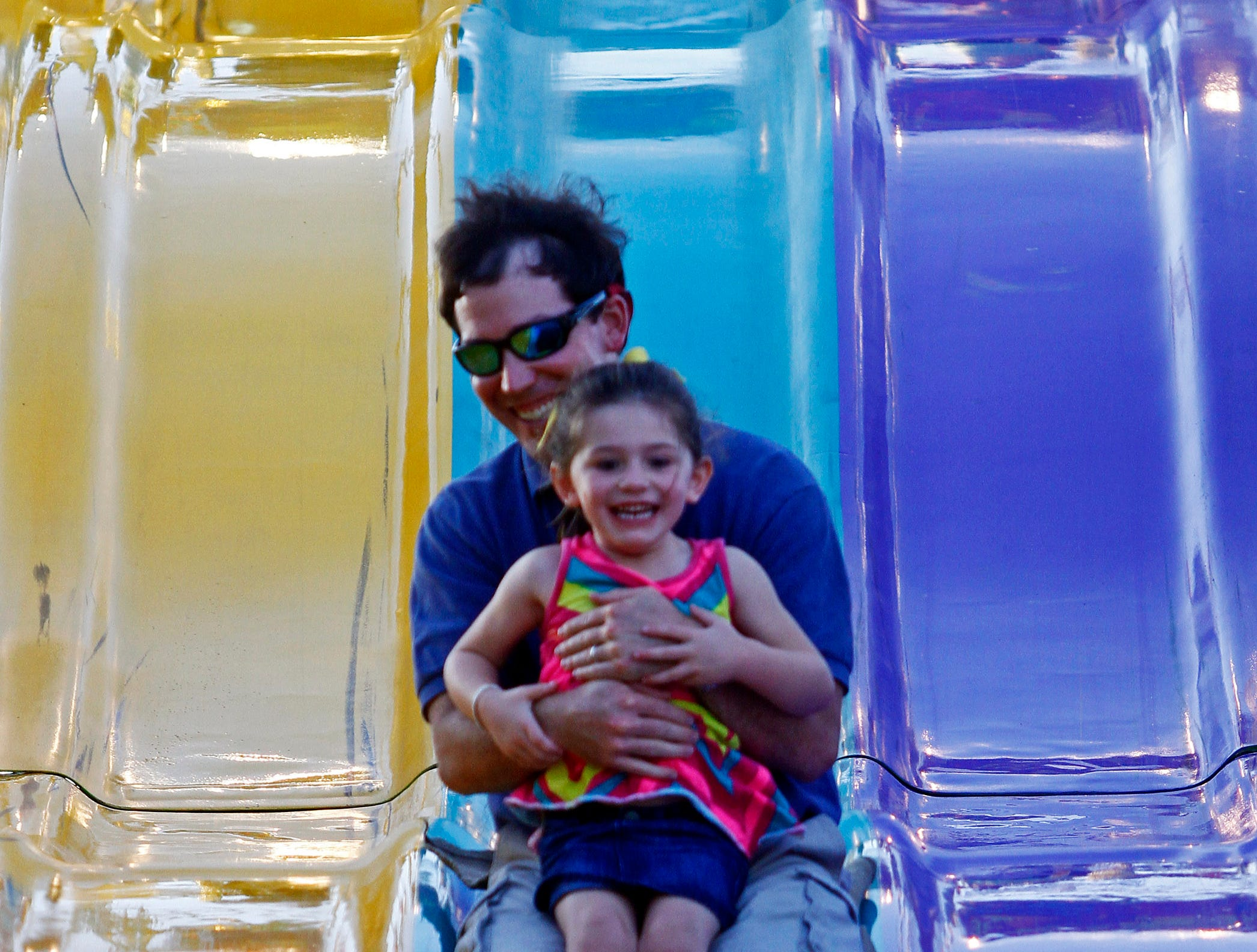 Scott Ellis goes down a slide with his 3-1/2 year-old daughter Mary Caroline during the first night of the annual Tennessee Valley Fair Friday, Sept. 7, 2012 in Knoxville, Tenn.