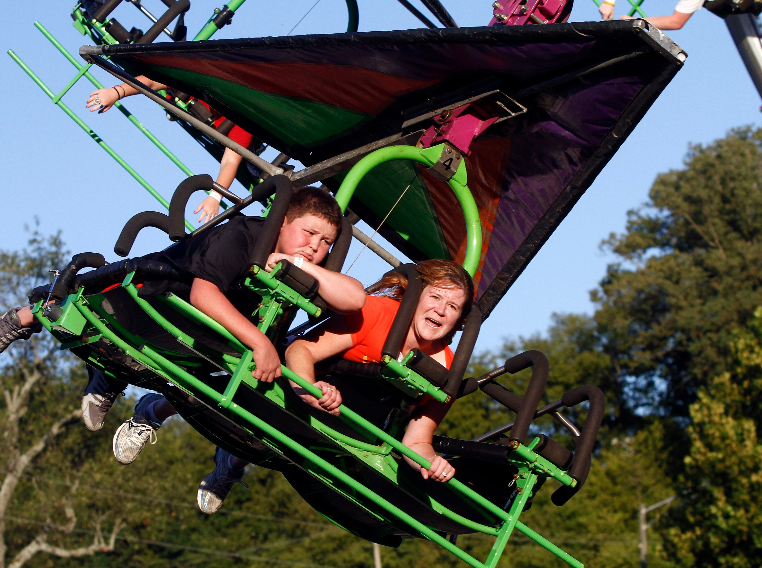 Two young people ride a ride that simulates a hang-glider during the first night of the annual Tennessee Valley Fair Friday, Sept. 7, 2012 in Knoxville, Tenn.