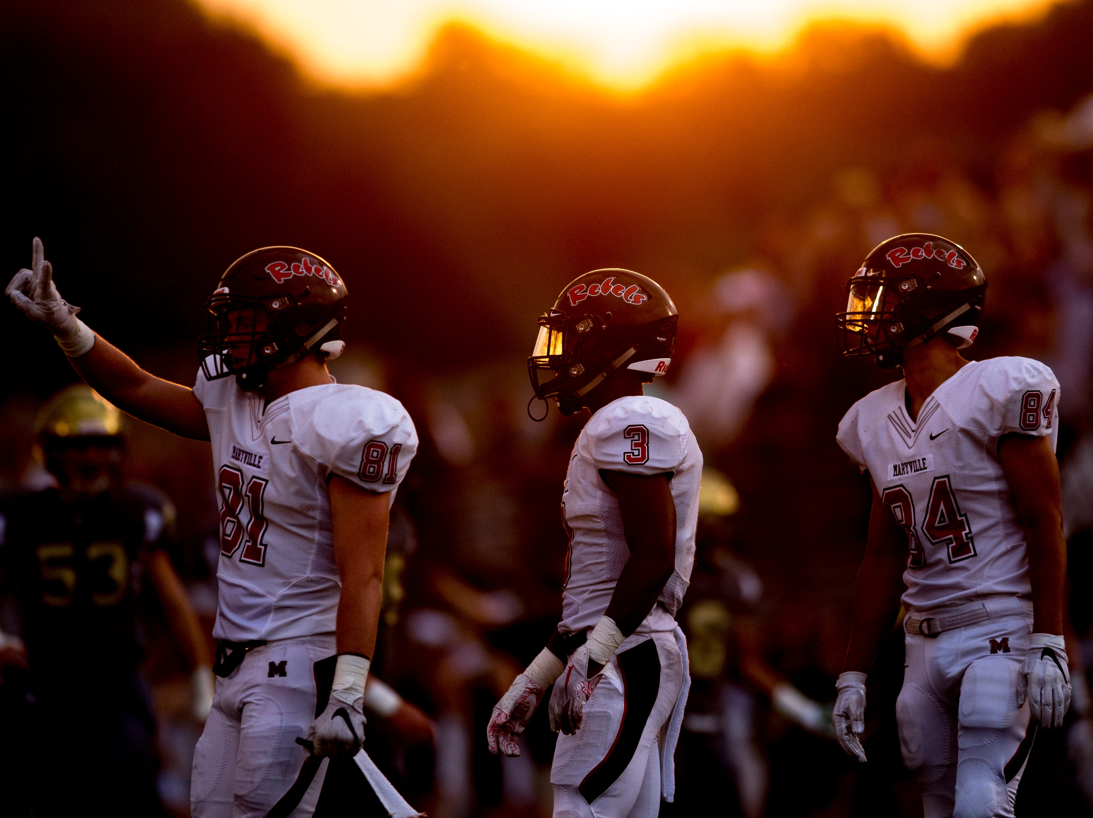 Maryville's Brody Sloan (81), Maryville's A.J. Davis (3) and Maryville's Brayden Anderson (84) on the field as the sun sets behind them during a football game between Maryville and Catholic at Catholic High School in Knoxville, Tennessee on Friday, August 17, 2018.