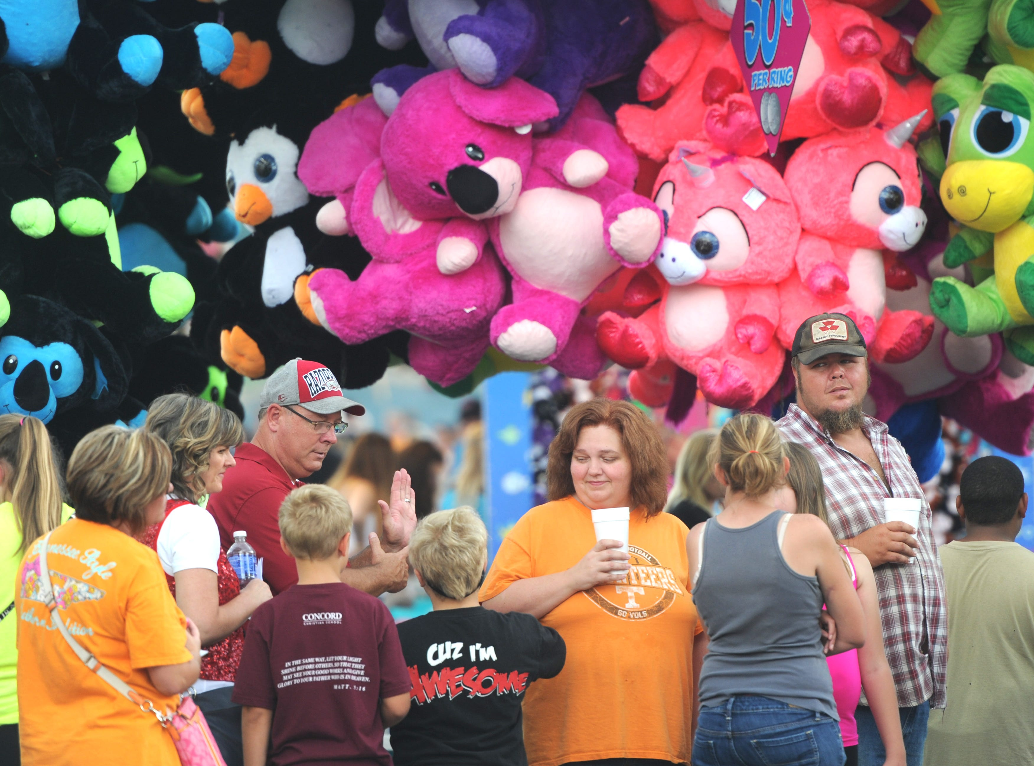 Fairgoers wait in line to buy ride tickets during the Tennessee Valley Fair's opening day at Chilhowee Park on Friday, Sept. 11, 2015.