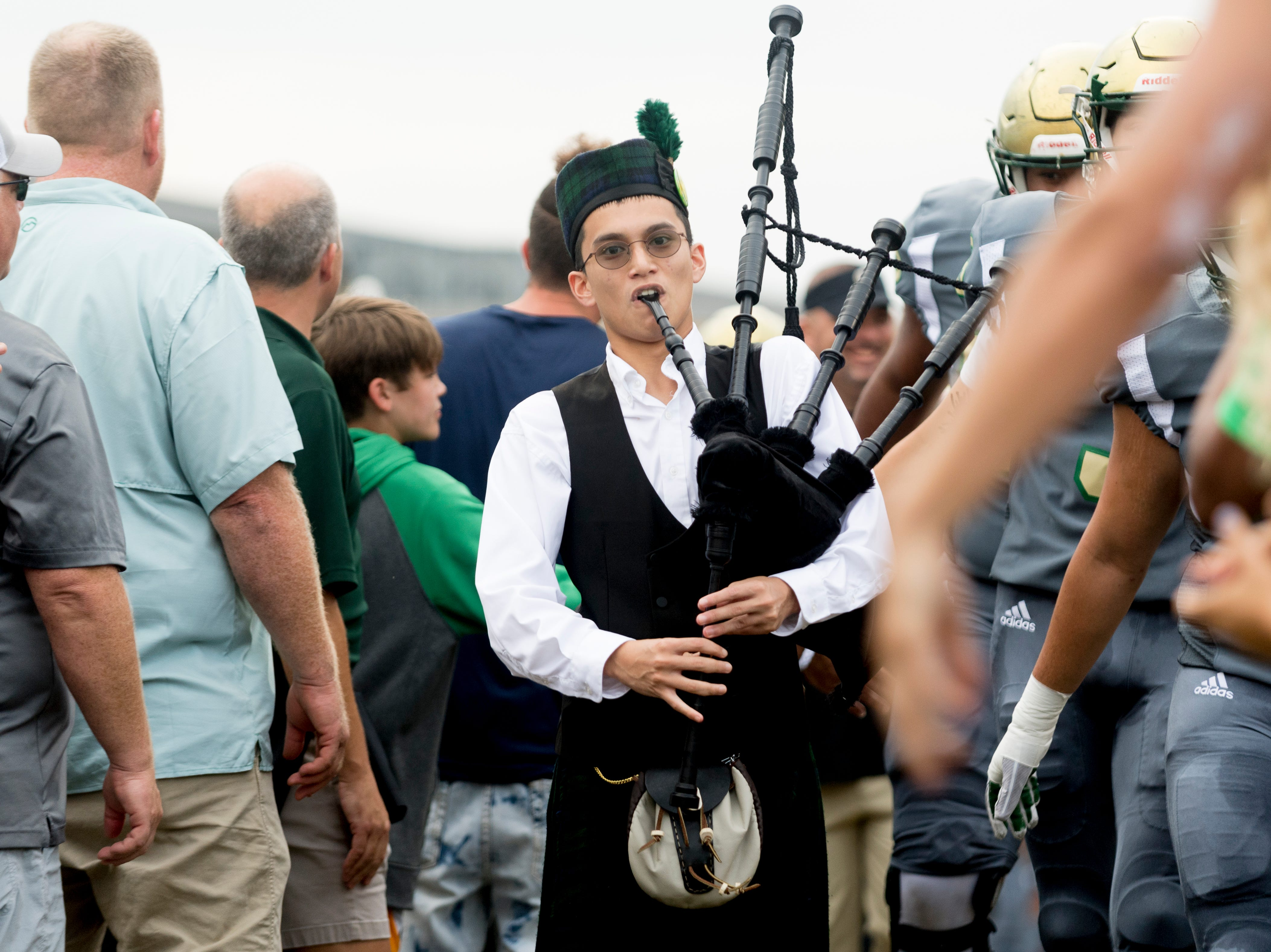 A bagpipe player escorts the team from the locker room during a football game between Maryville and Catholic at Catholic High School in Knoxville, Tennessee on Friday, August 17, 2018.