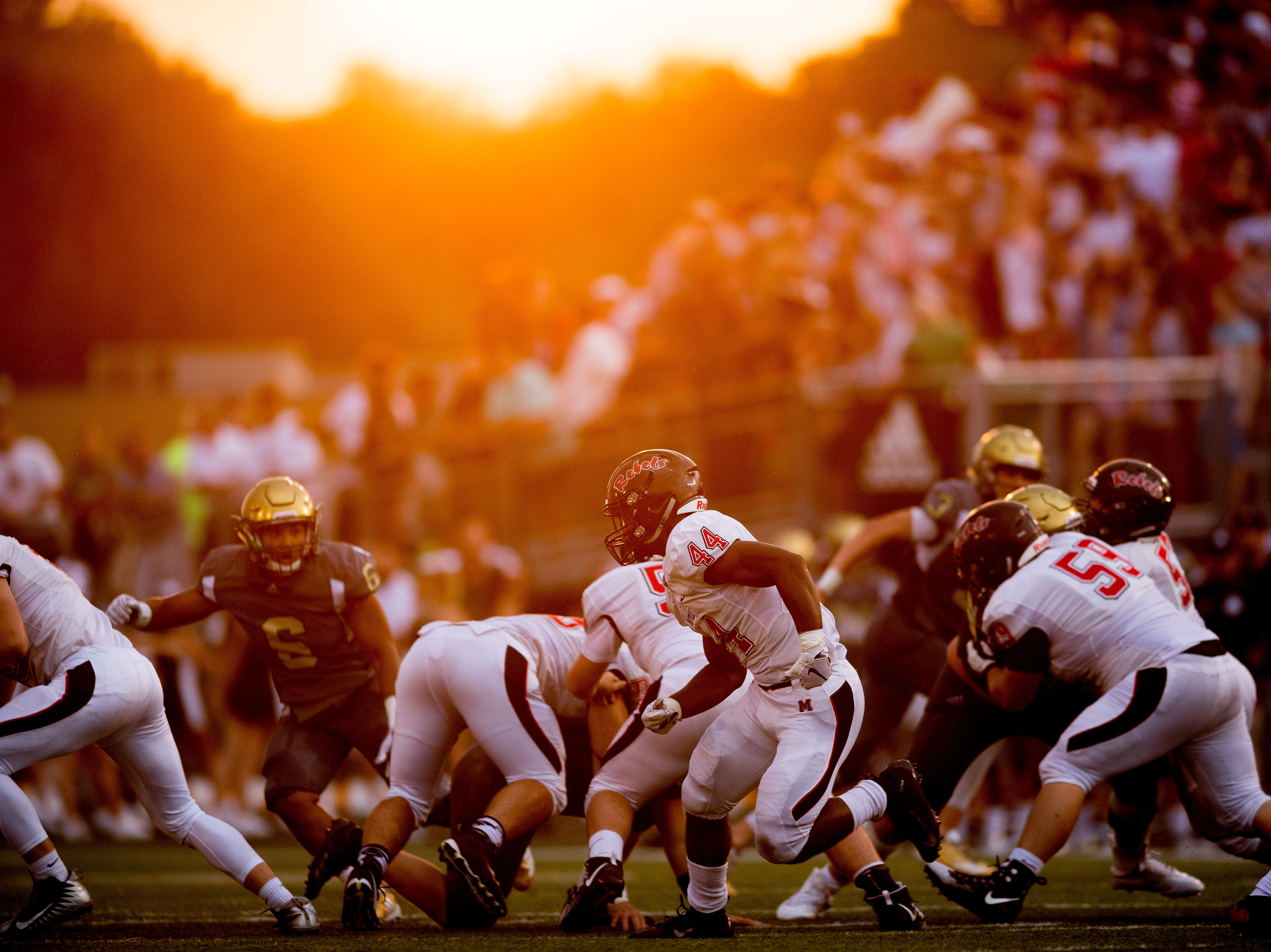 The sun sets over players during a football game between Maryville and Catholic at Catholic High School in Knoxville, Tennessee on Friday, August 17, 2018.