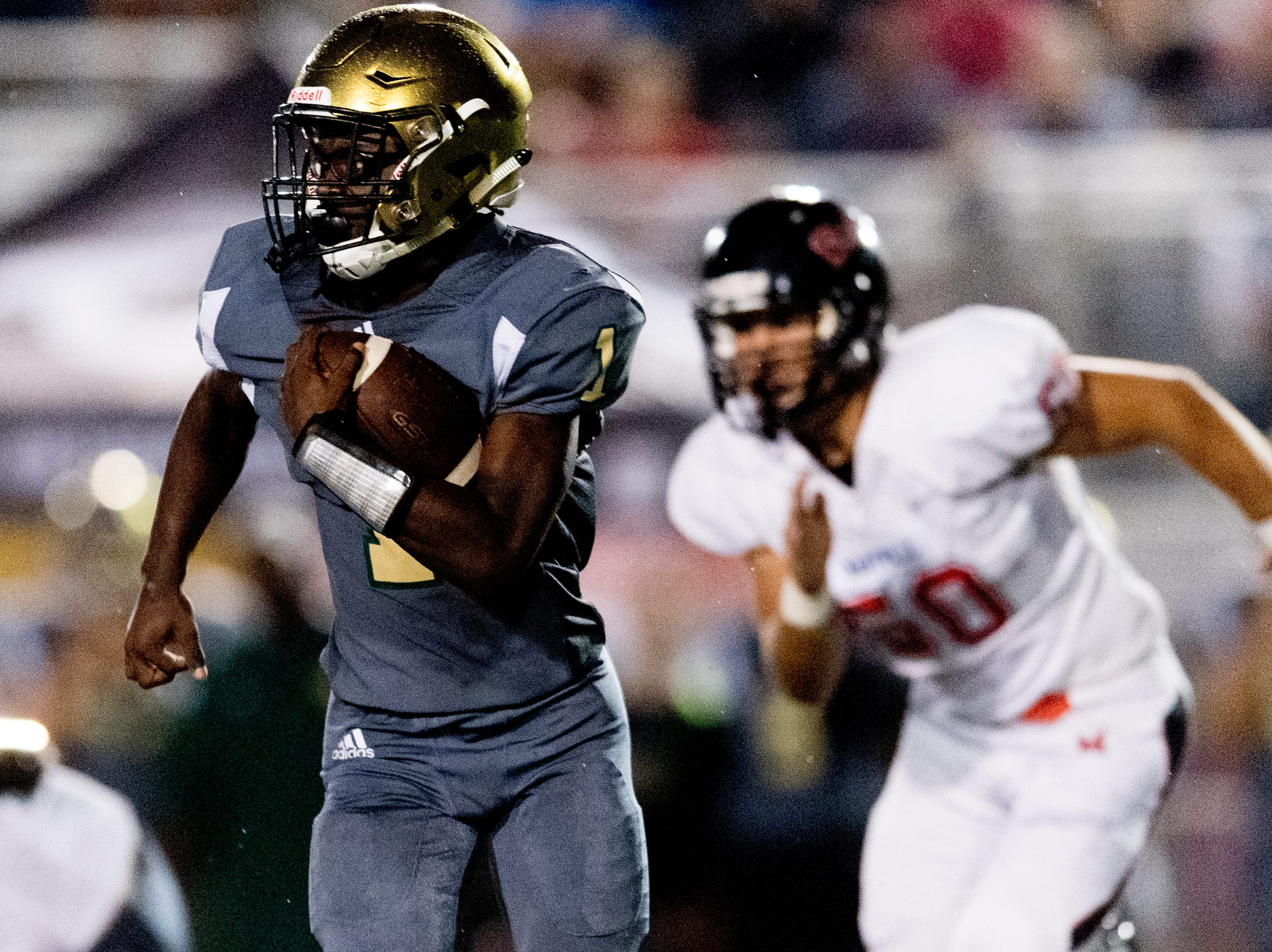 Catholic's Keondre' Jarmon (1) runs the ball as Maryville's Colton Peek (50) pursues during a football game between Maryville and Catholic at Catholic High School in Knoxville, Tennessee on Friday, August 17, 2018.
