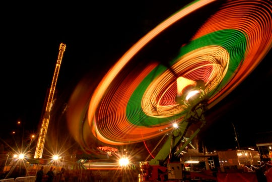 Bright lights from spinning thrill rides make for a colorful scene on the midway at the Tennessee Valley Fair at Chilhowee Park in 2007.