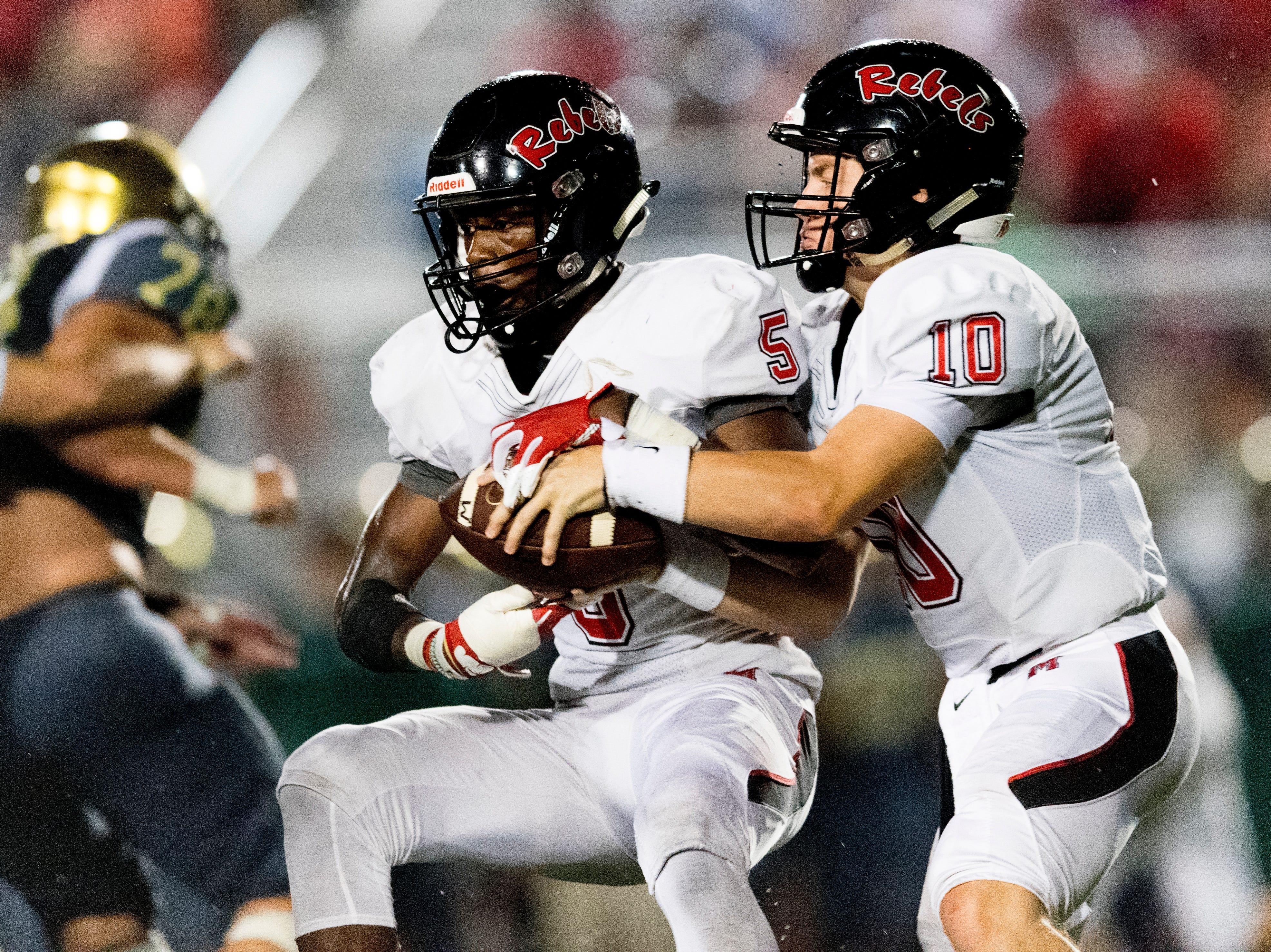 Maryville's Braden Carnes (10) hands the ball off to Maryville's DaVon Kimble (5) during a football game between Maryville and Catholic at Catholic High School in Knoxville, Tennessee on Friday, August 17, 2018.