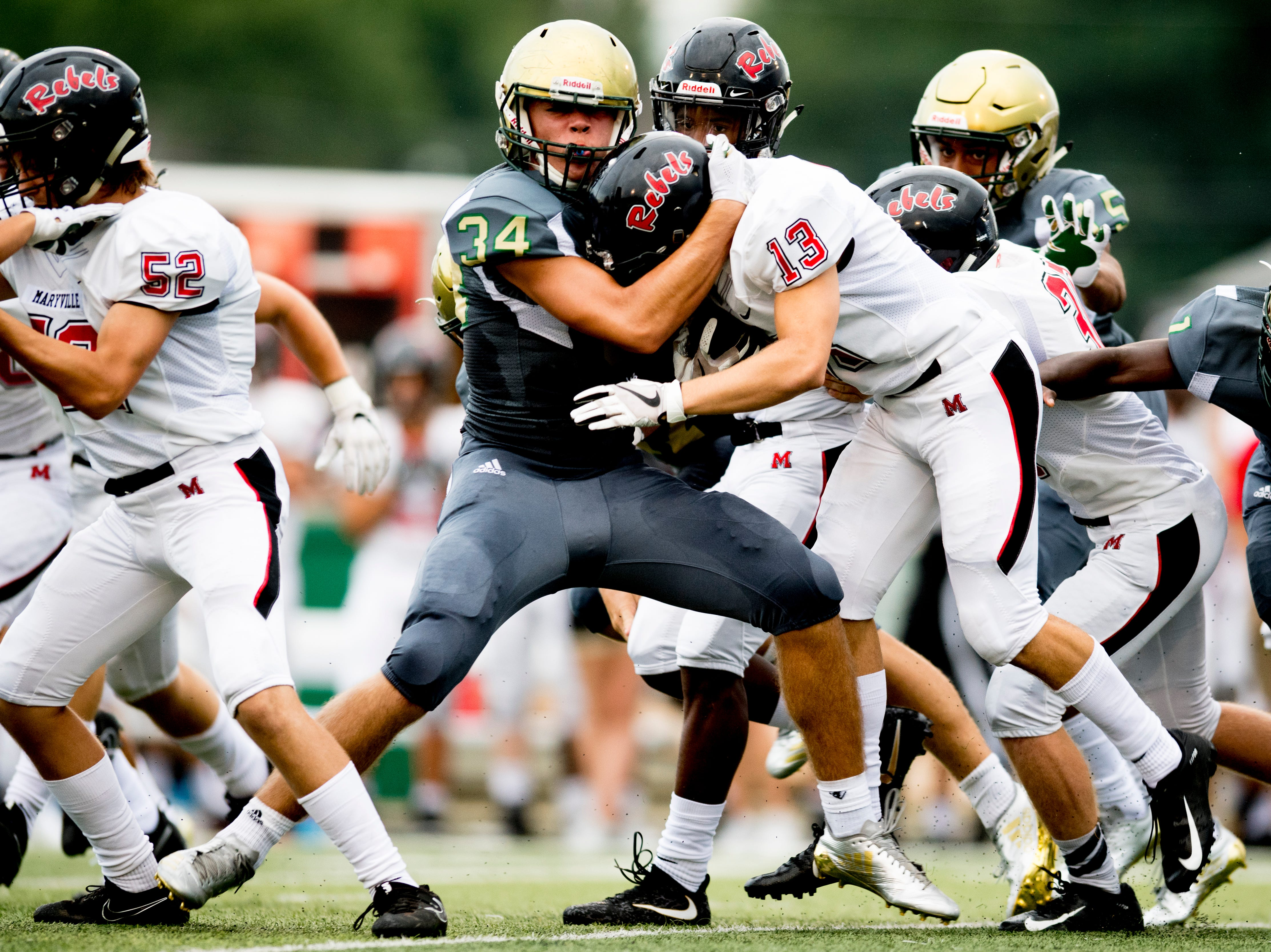 Catholic's Luke Davenport (34) takes down Maryville's Jackson Jett (13) during a football game between Maryville and Catholic at Catholic High School in Knoxville, Tennessee on Friday, August 17, 2018.