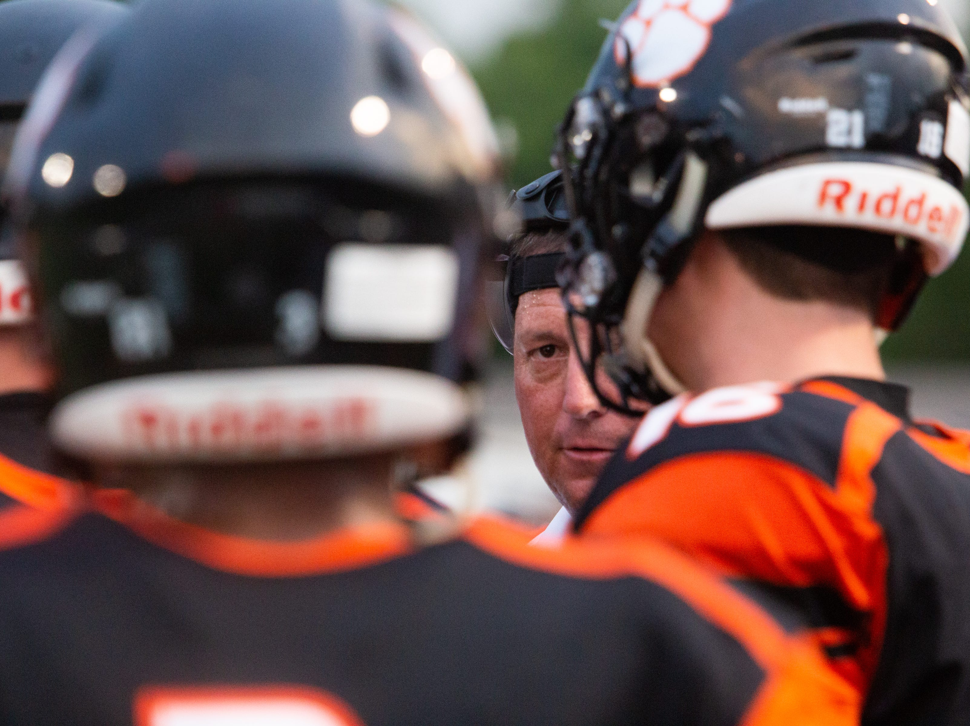 Powell head coach Matt Lowe talks with his players during the Powell versus Halls football game at Powell High School Friday, Aug. 17, 2018.