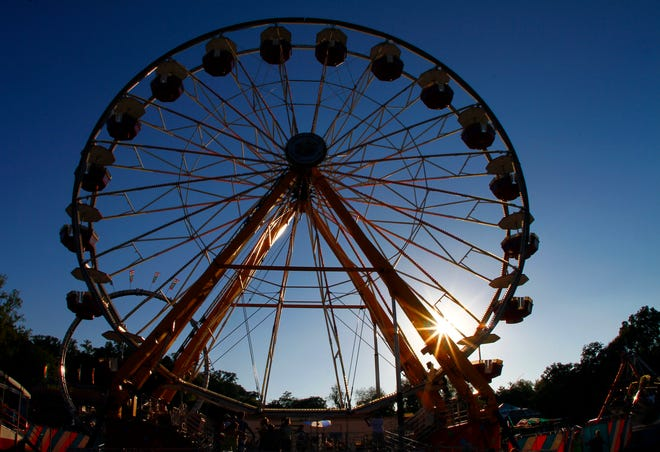 People ride the Ferris Wheel as the sun sets during the first night of the annual Tennessee Valley Fair Friday, Sept. 7, 2012 in Knoxville, Tenn.