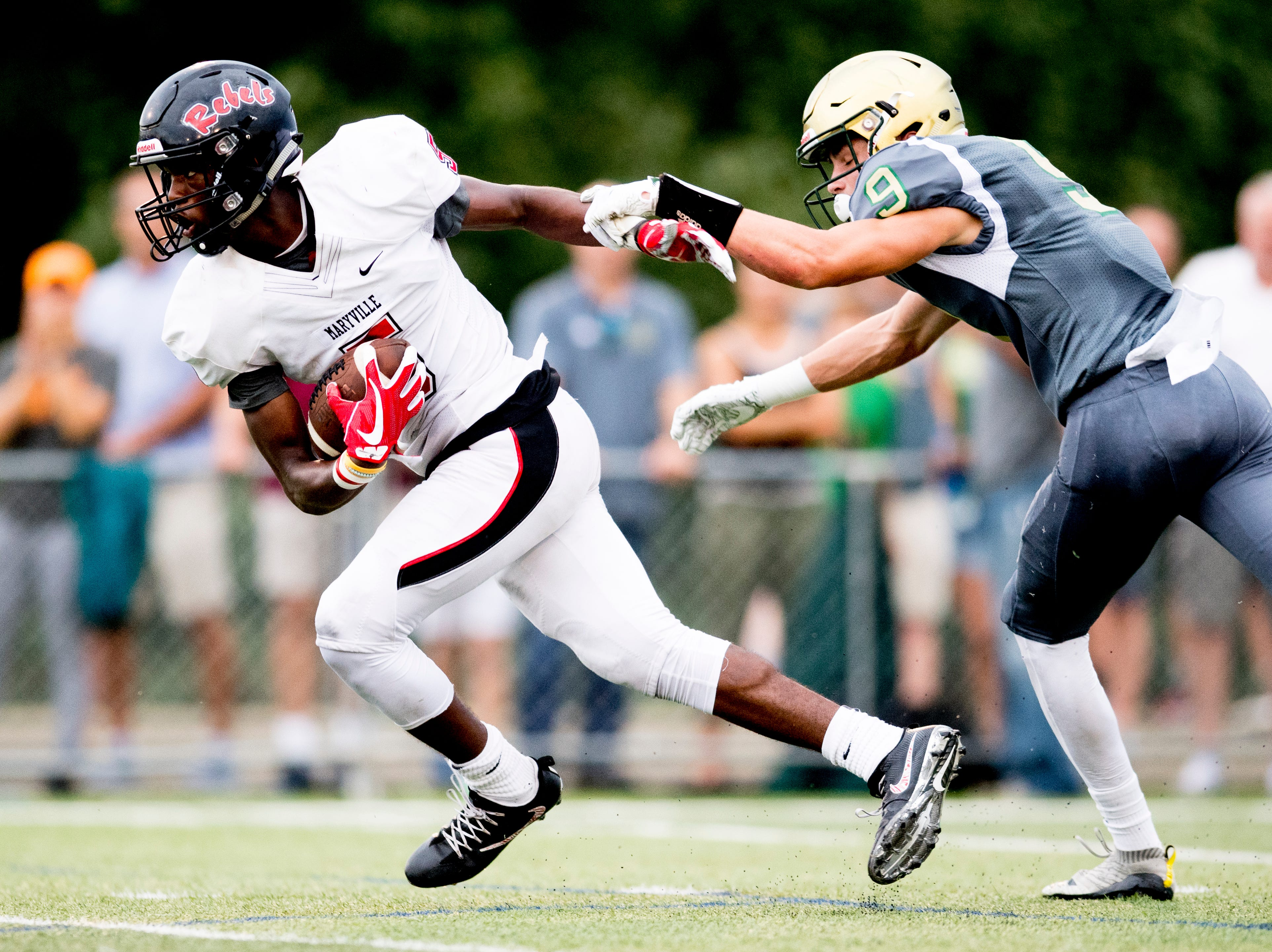 Maryville's DaVon Kimble (5) runs past Catholic's Adam Jones (9) during a football game between Maryville and Catholic at Catholic High School in Knoxville, Tennessee on Friday, August 17, 2018.